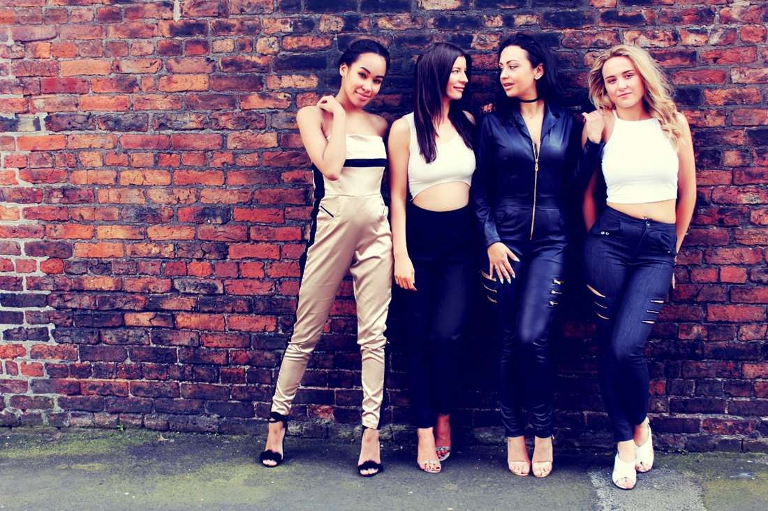 Four models leaning against a brick wall