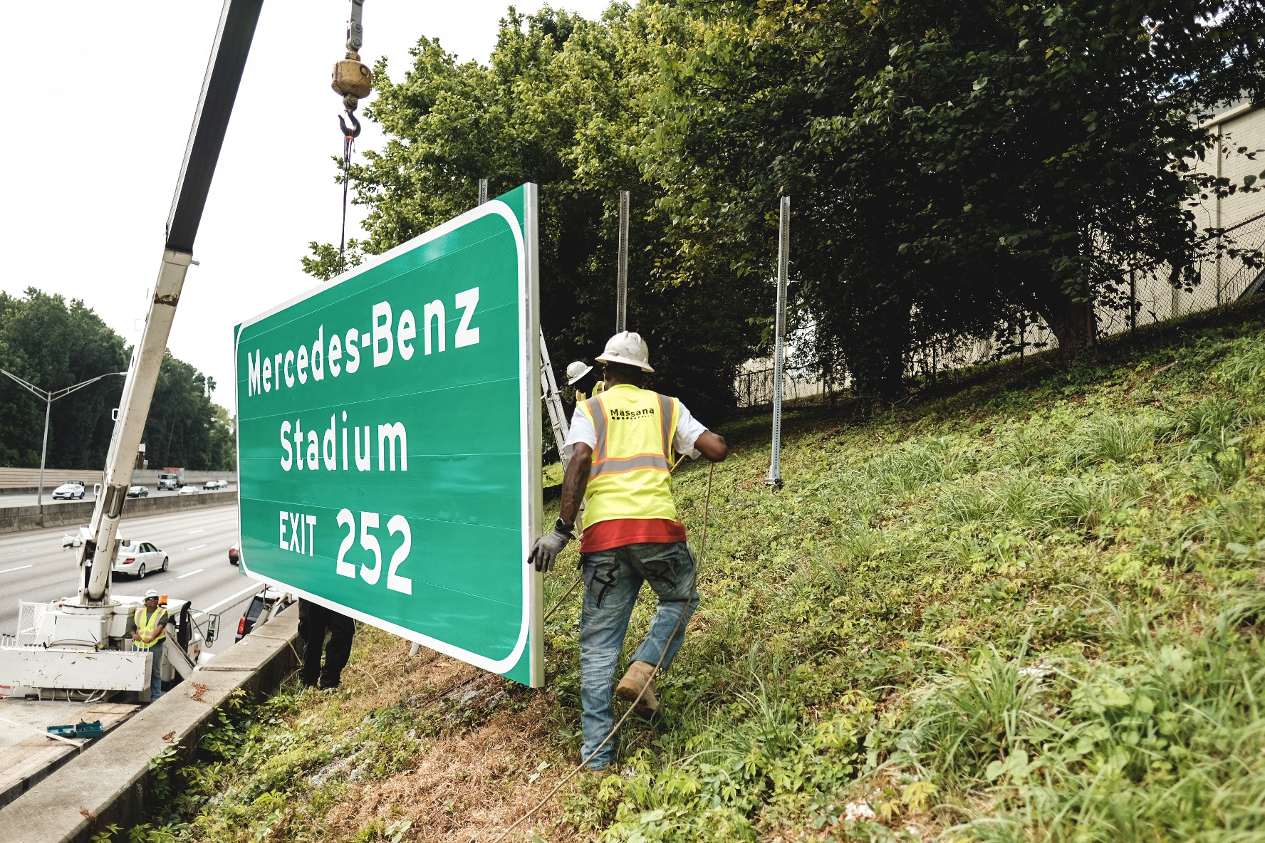 A new sign for Mercedes-Benz Stadium being installed along an Atlanta freeway.