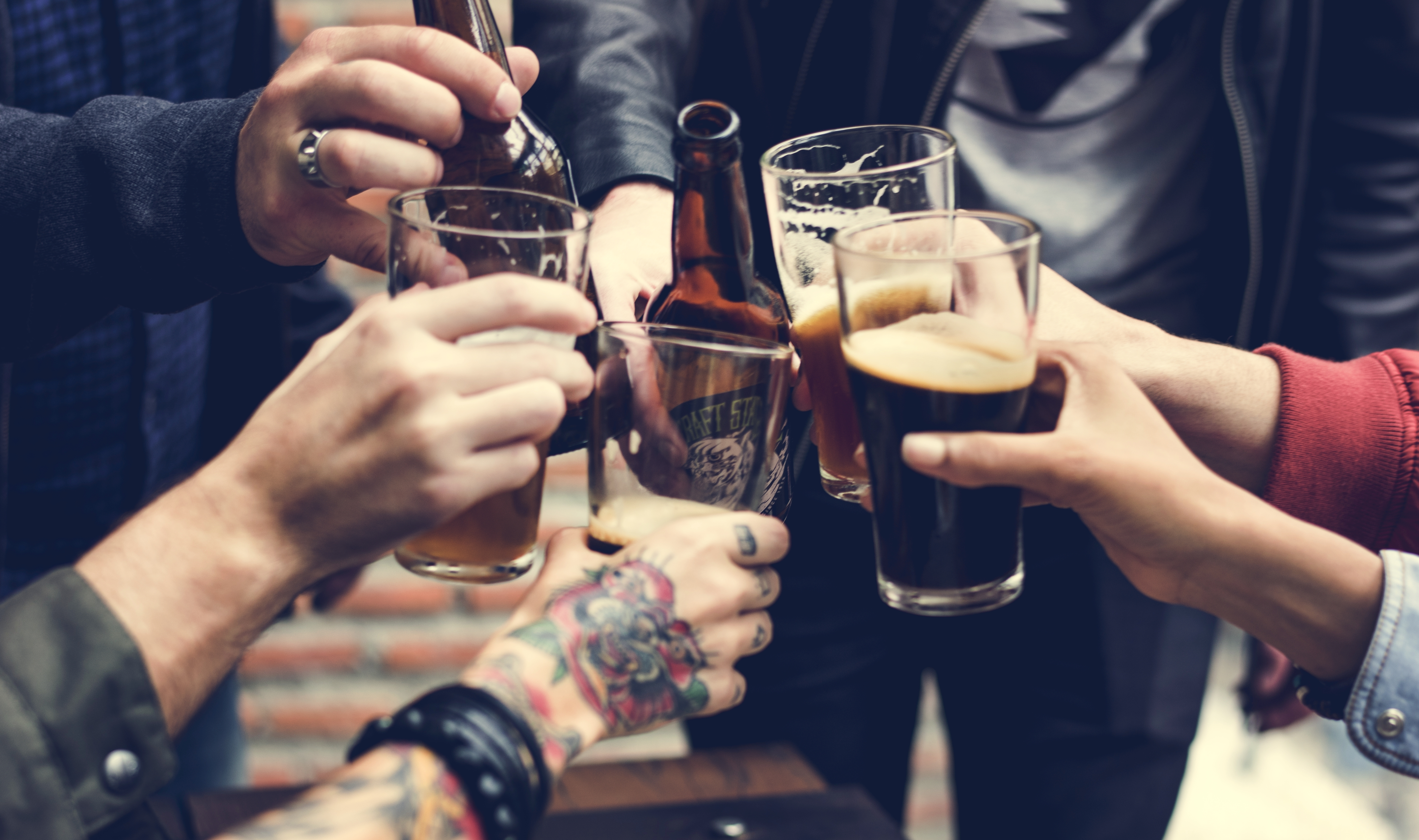 multiple hands holding beers and cheers-ing