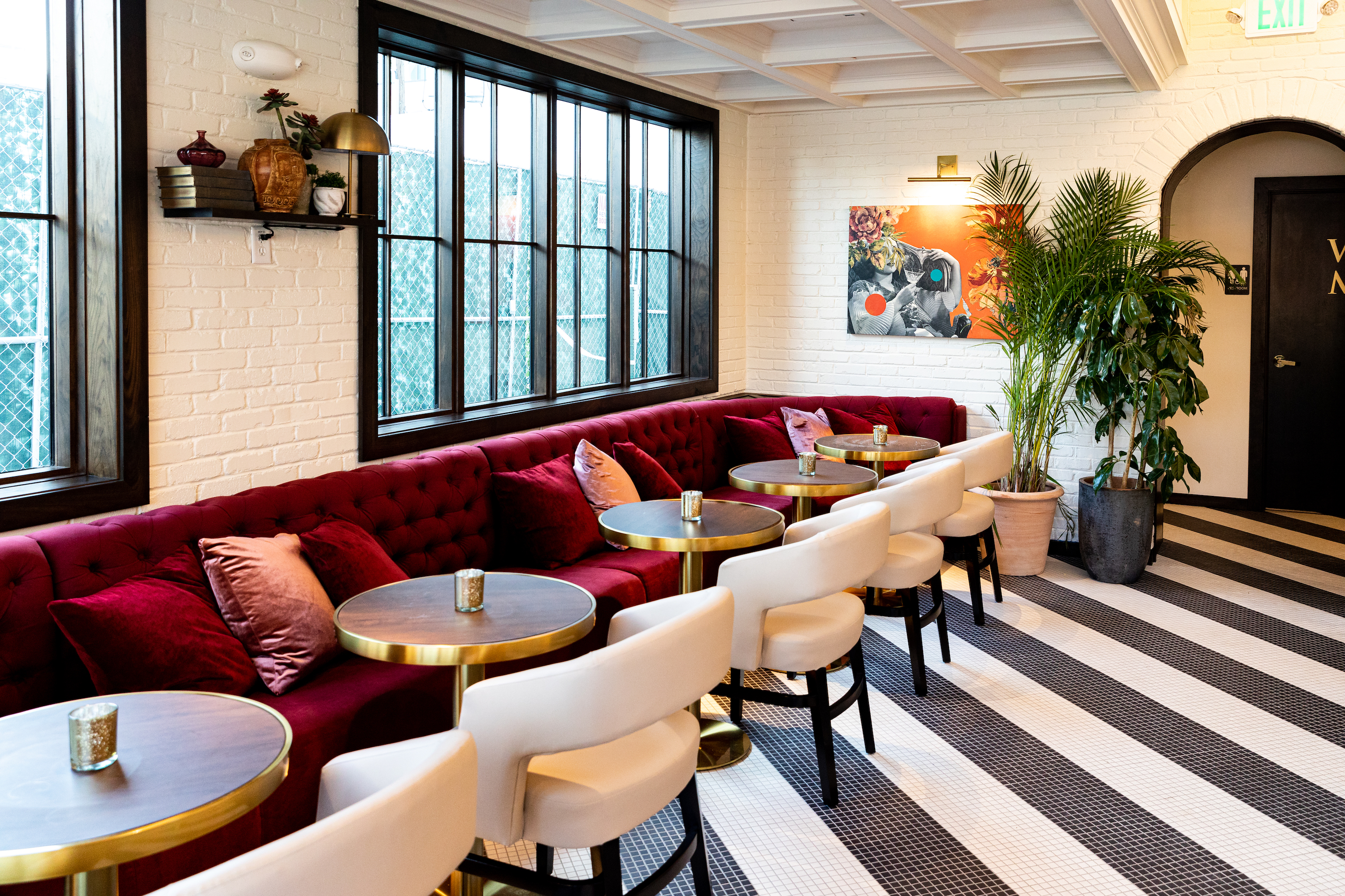 Bar interior with red banquettes, potted plants, and tile floors