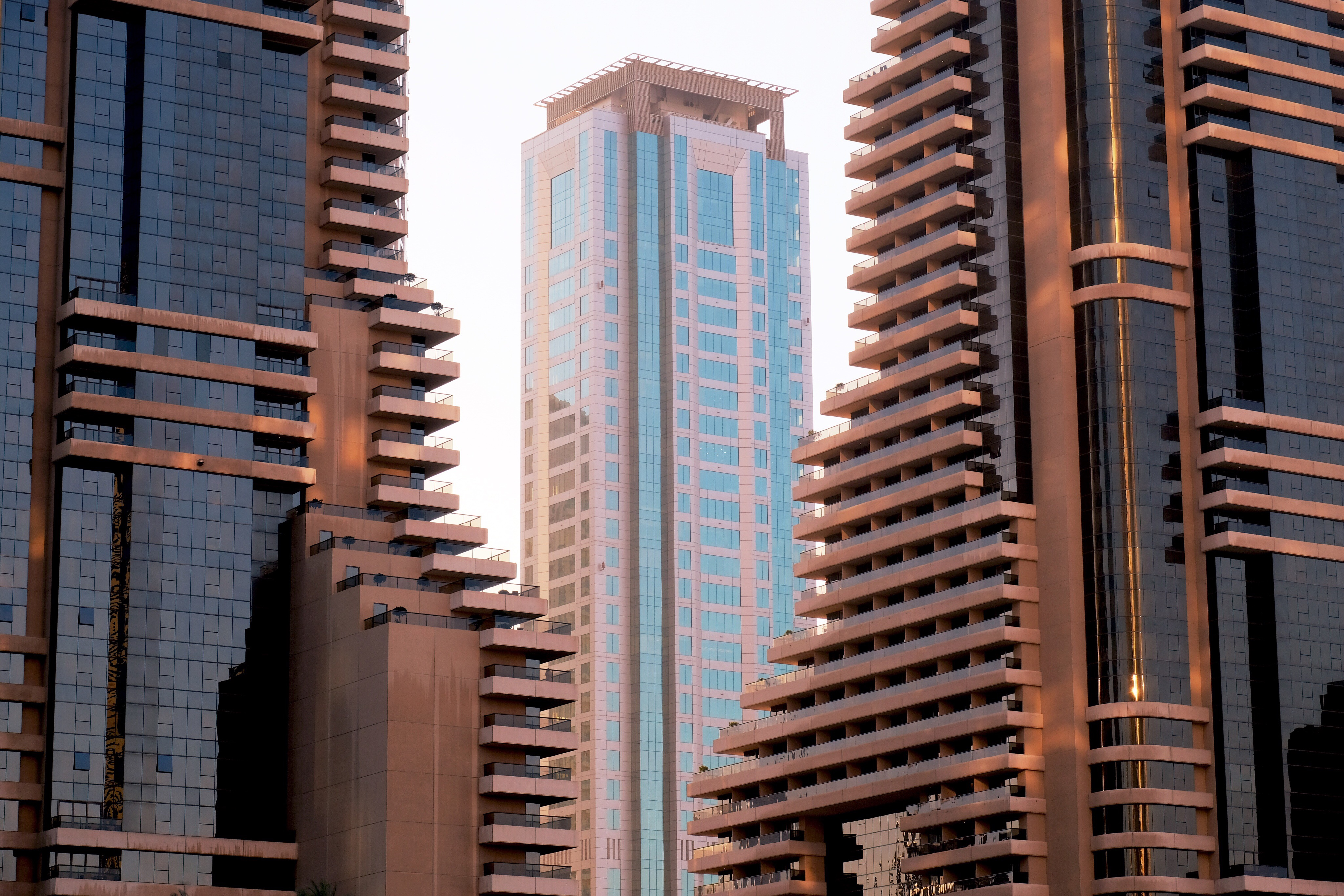 Photo of a skyscraper in the background flanked by two buildings on either side in the foreground.