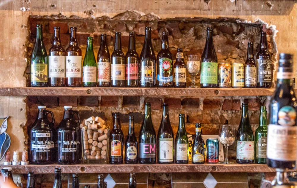 Two shelves on a brick wall with glasses of beer