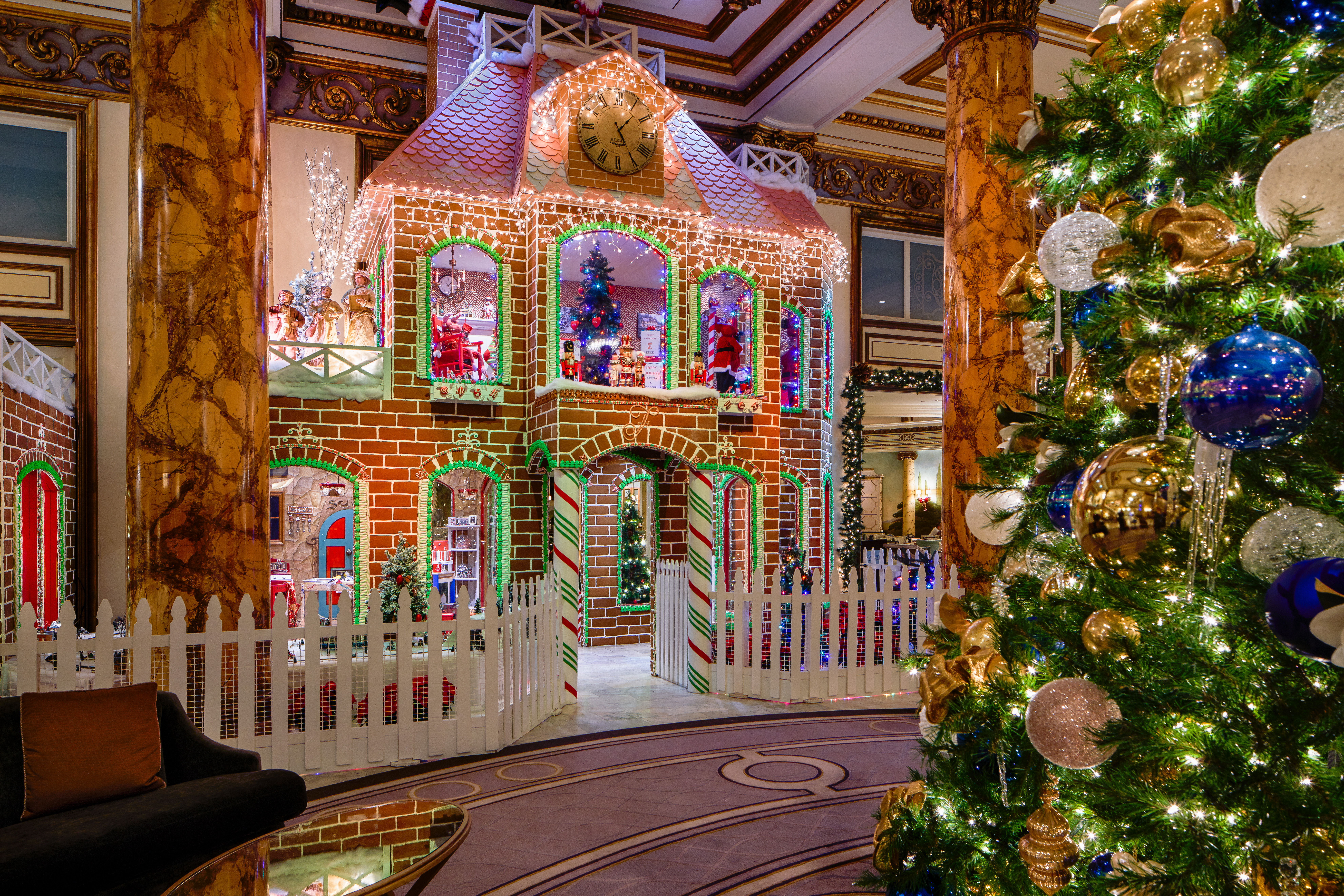 A two-story gingerbread house with lights, frosting, and edible bricks in the middle of a hotel lobby.
