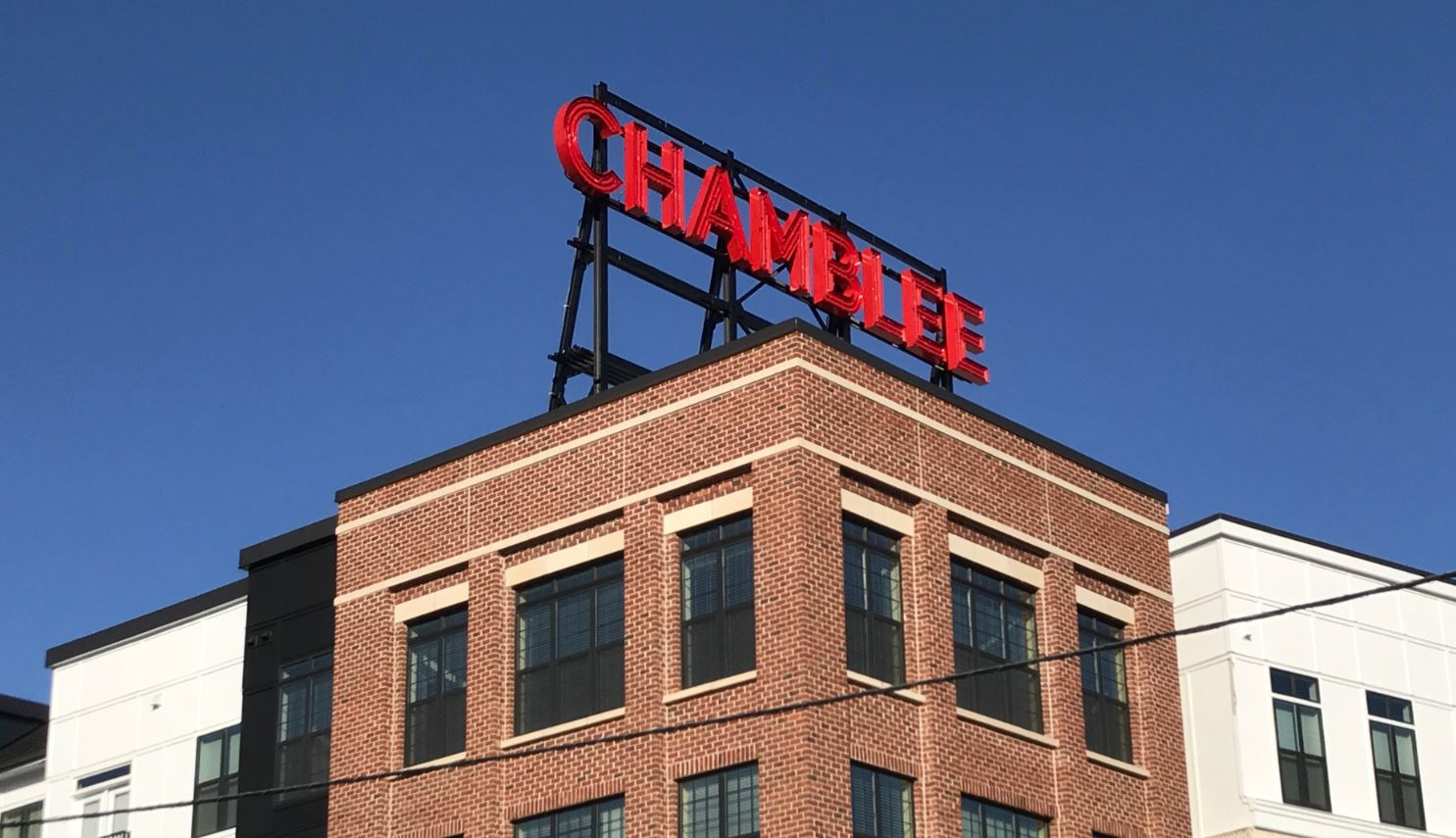 """A lighted red sign atop the apartment building that says """"CHAMBLEE."""""""