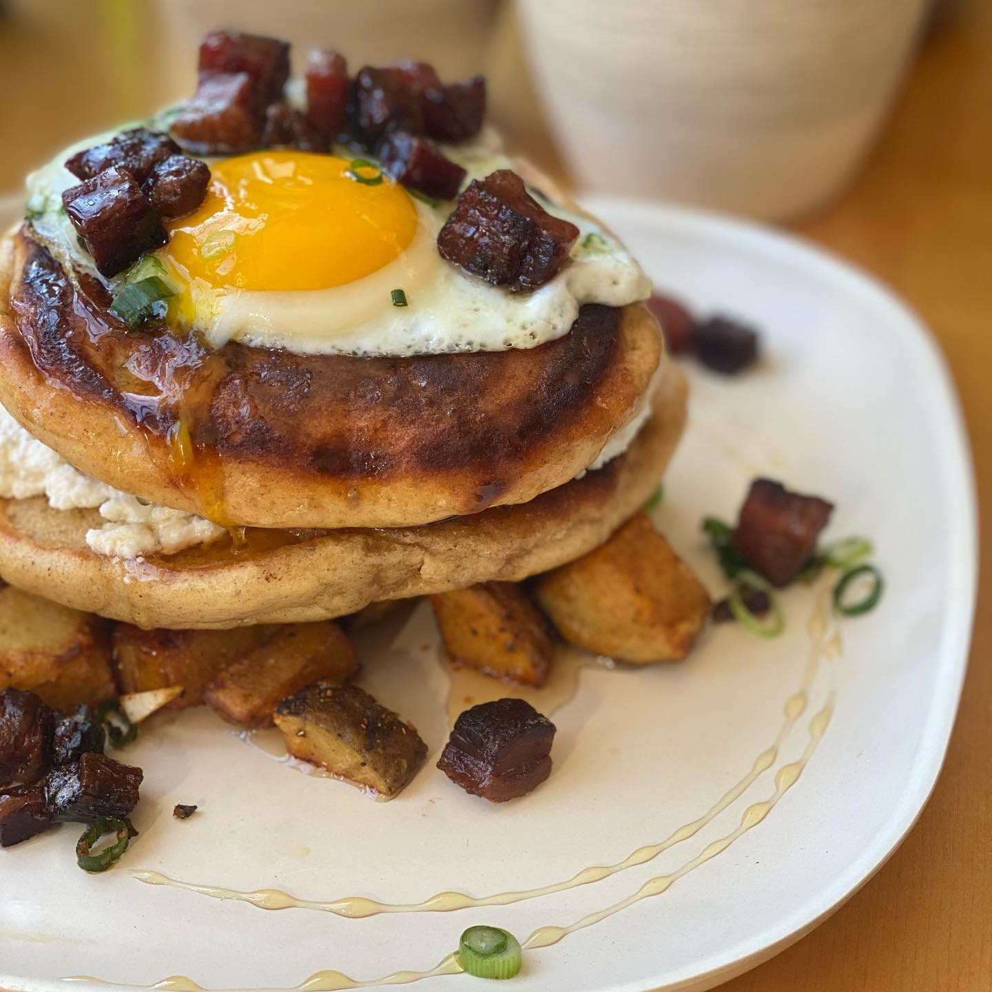 pancakes with sunny side up egg on top and bacon