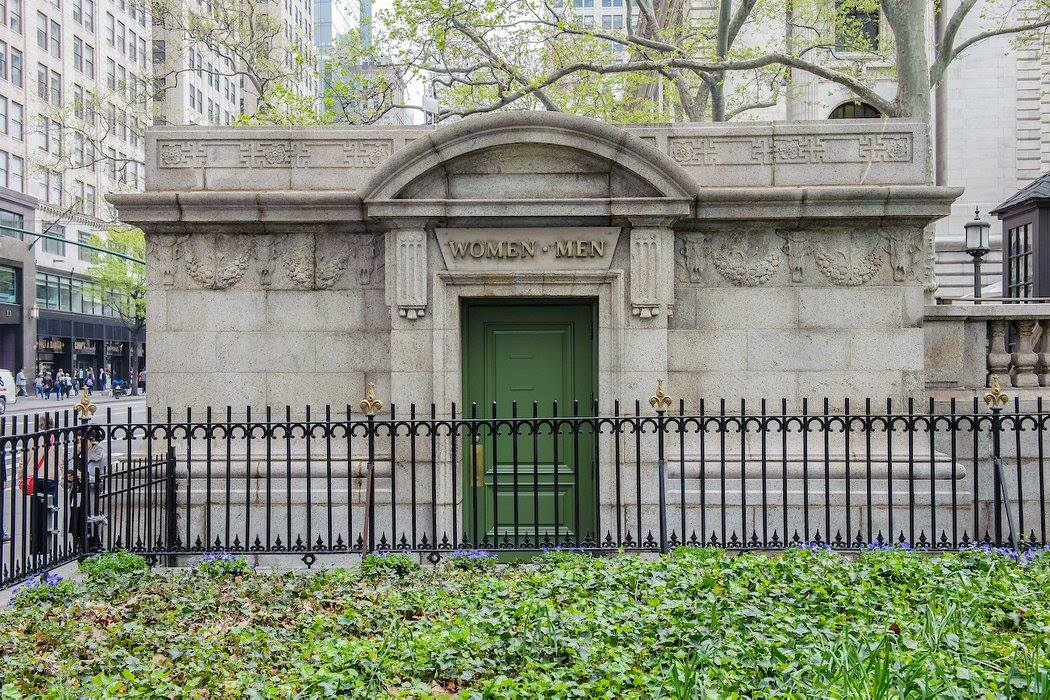 The exterior of a public bathroom in Bryant Park. The facade is concrete and the door is arched.