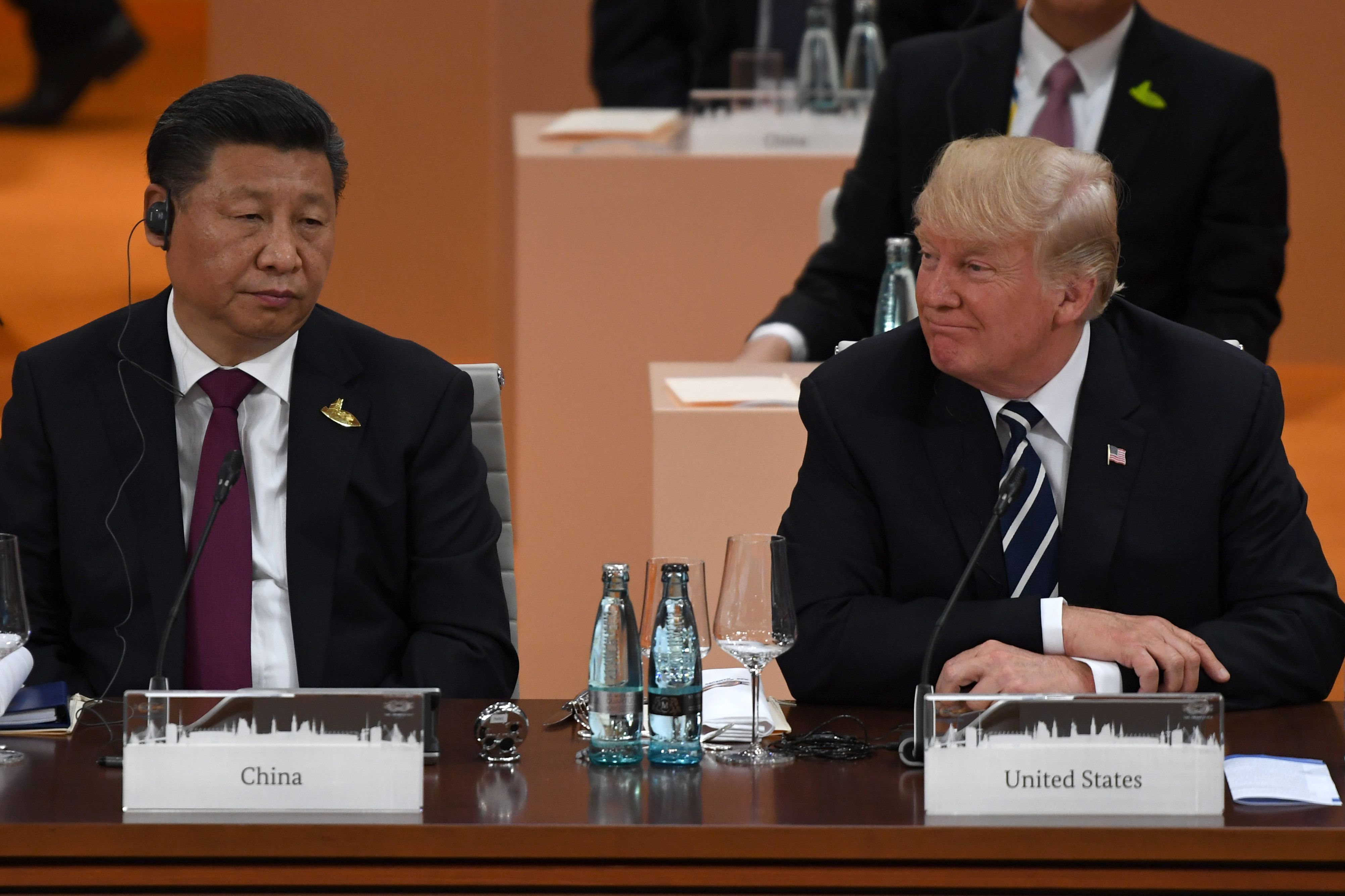 """Xi Jinping and President Trump sit next to each other at a table with placards saying """"China"""" and """"United States"""" in front of them."""