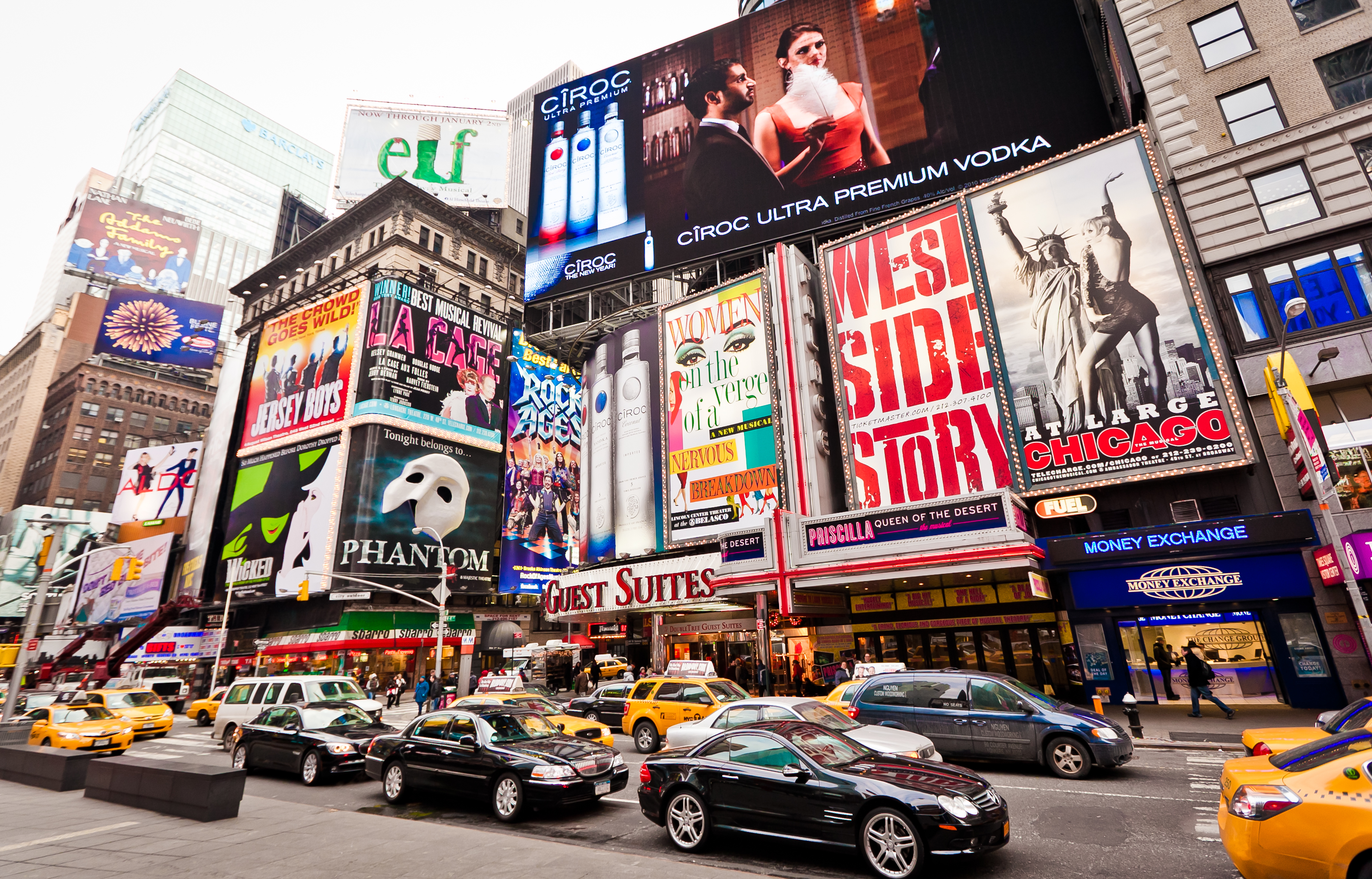 A street view of New York City's Theater District with many billboards of Broadway shows and a busy street filled with cars.