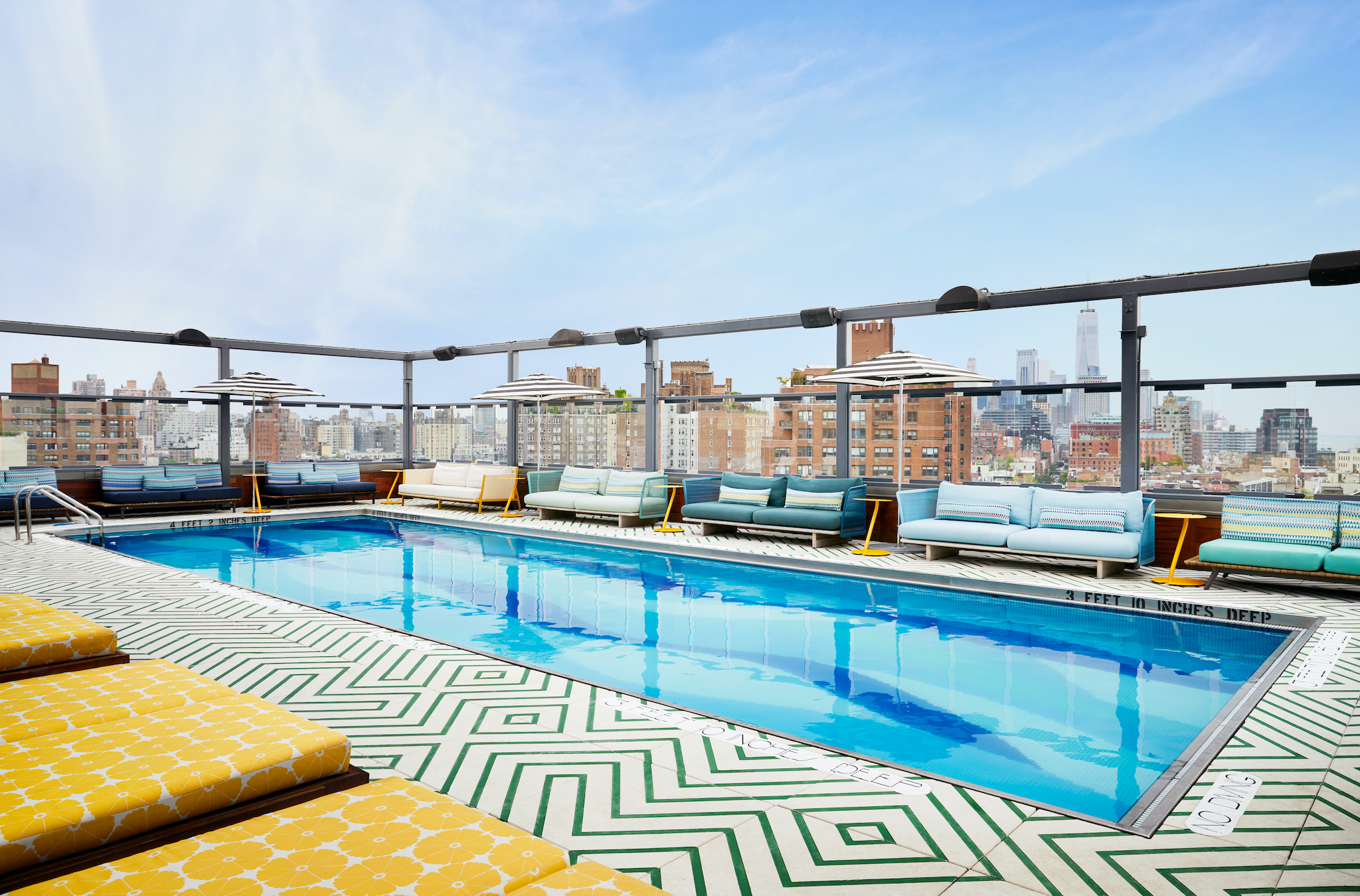 Outdoor furniture is set up around a pool with a patterned floor. In the background, a city skyline is visible.