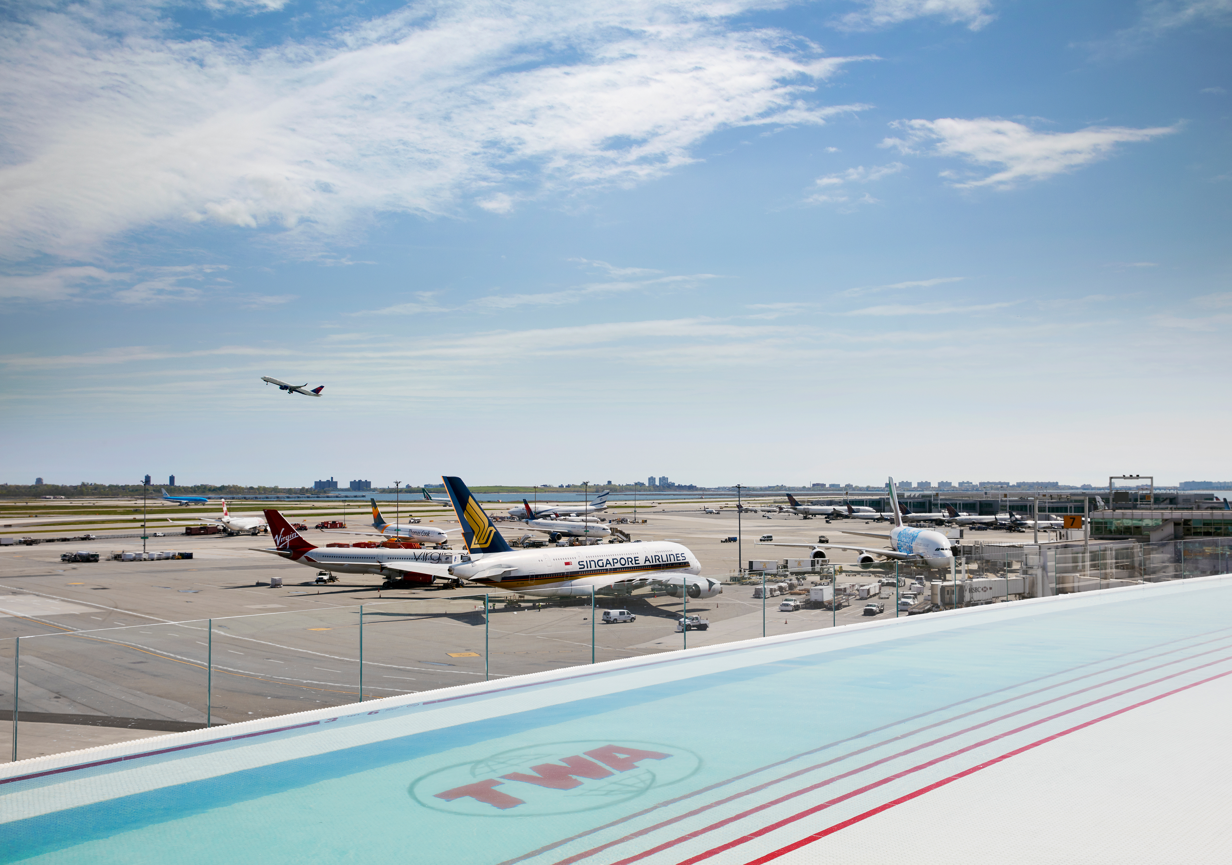 A swimming pool is in the foreground. The letters TWA are written on the bottom of the pool. In the distance are airplanes on an airport runway.
