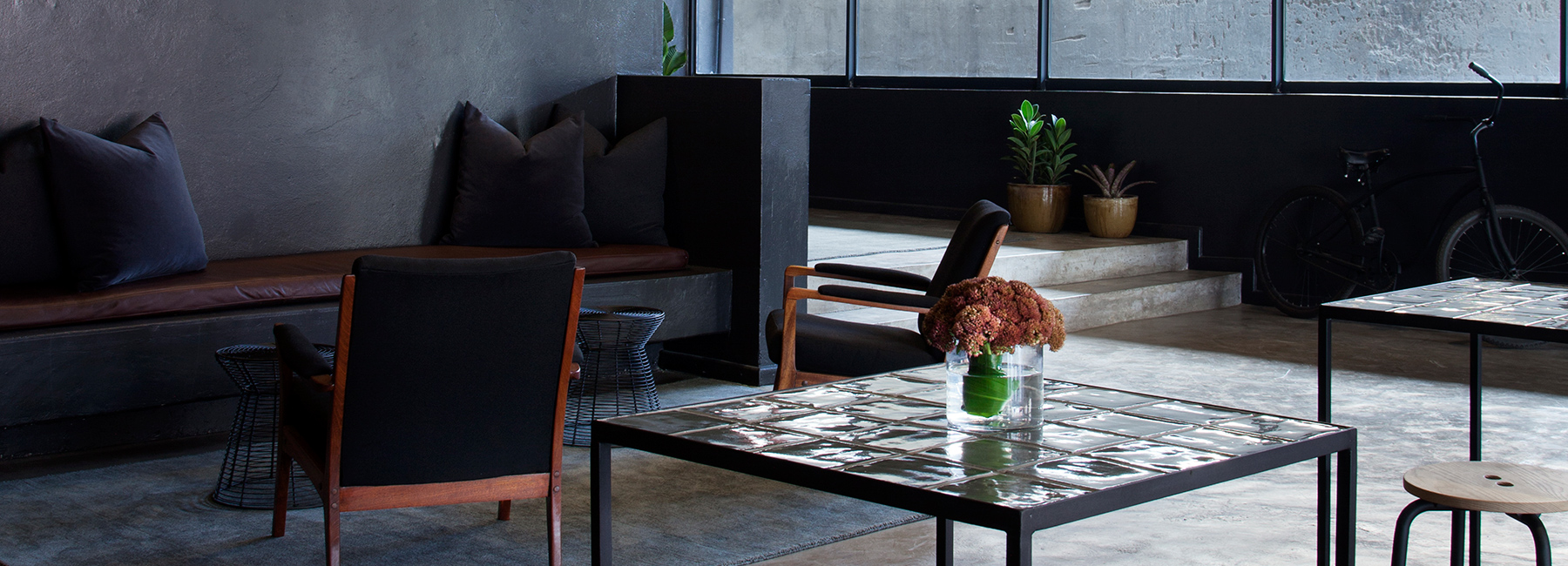 Interior shot of reception room with concrete floors, dark concrete walls, dark chairs, and two tiled coffee tables.