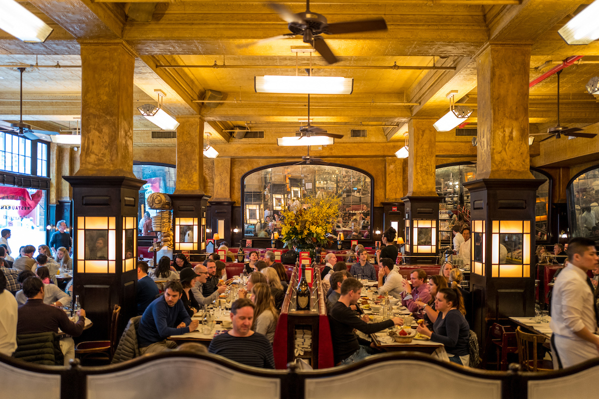 Balthazar's grand dining room with a mirror in the back and gold lighting