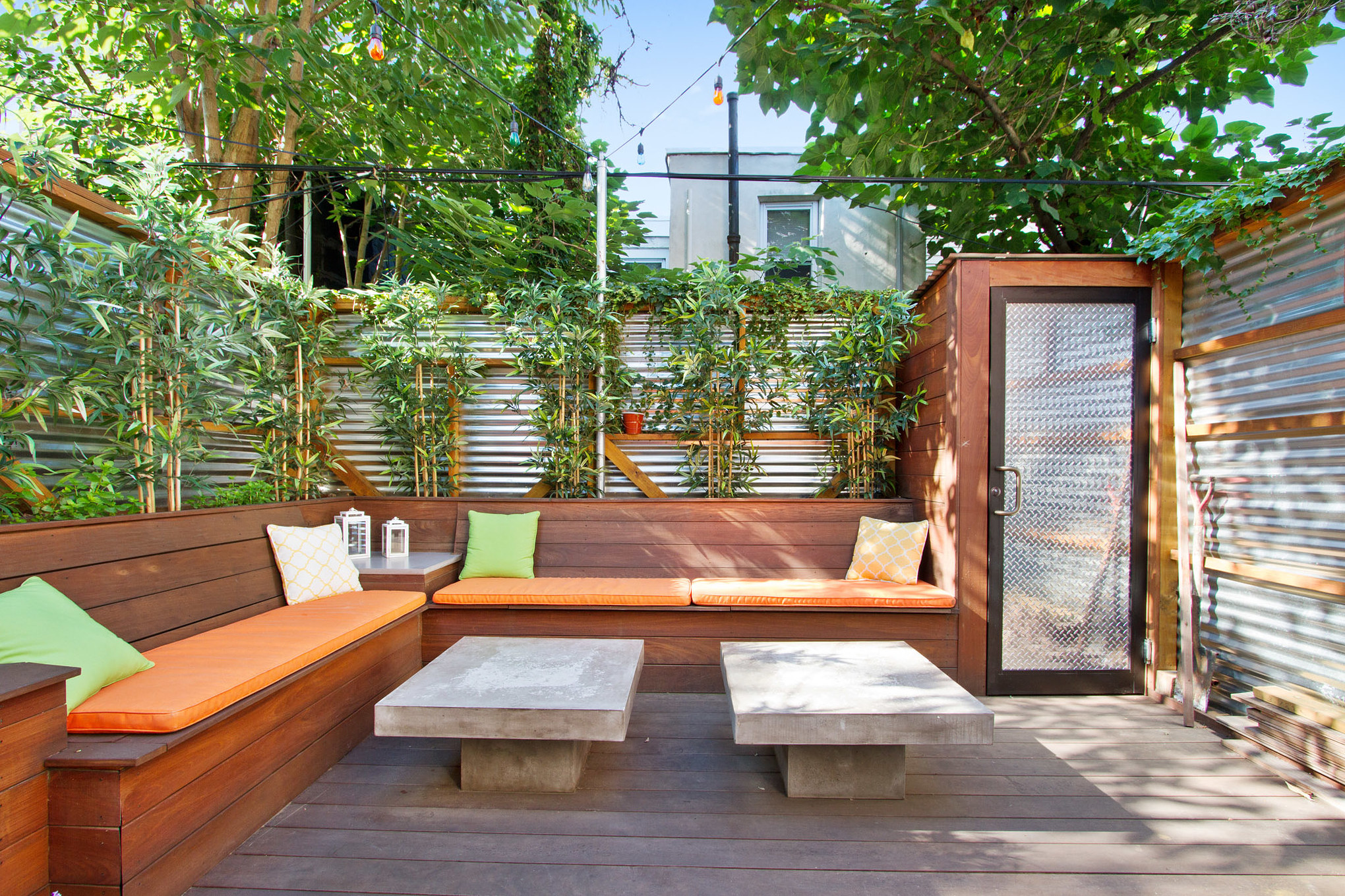 A landscaped backyard in Philadelphia with corrugated metal fences and built-in benches.