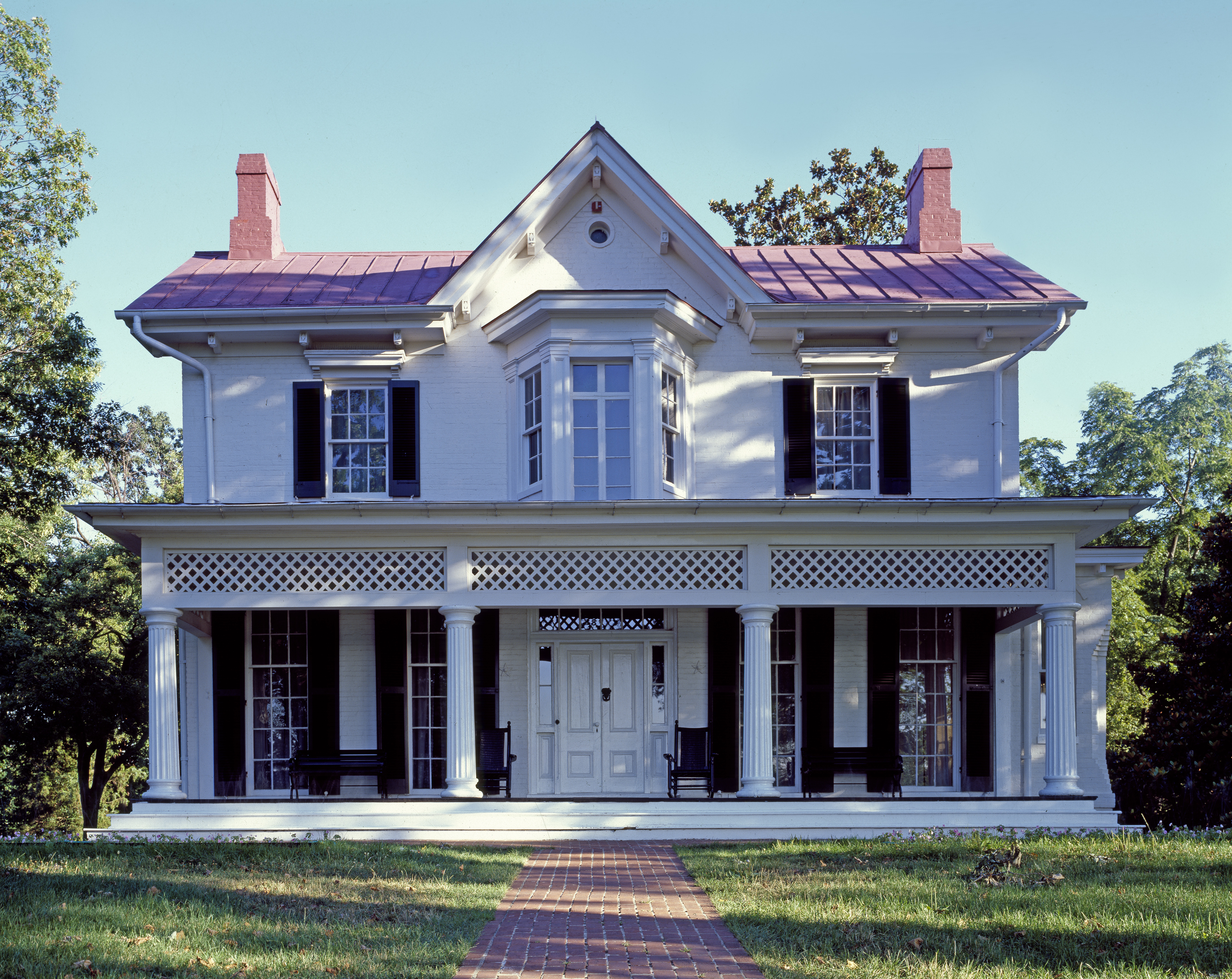 The exterior of the Frederick Douglass house in Washington D.C. The house is white with a pink roof and white columns in front.