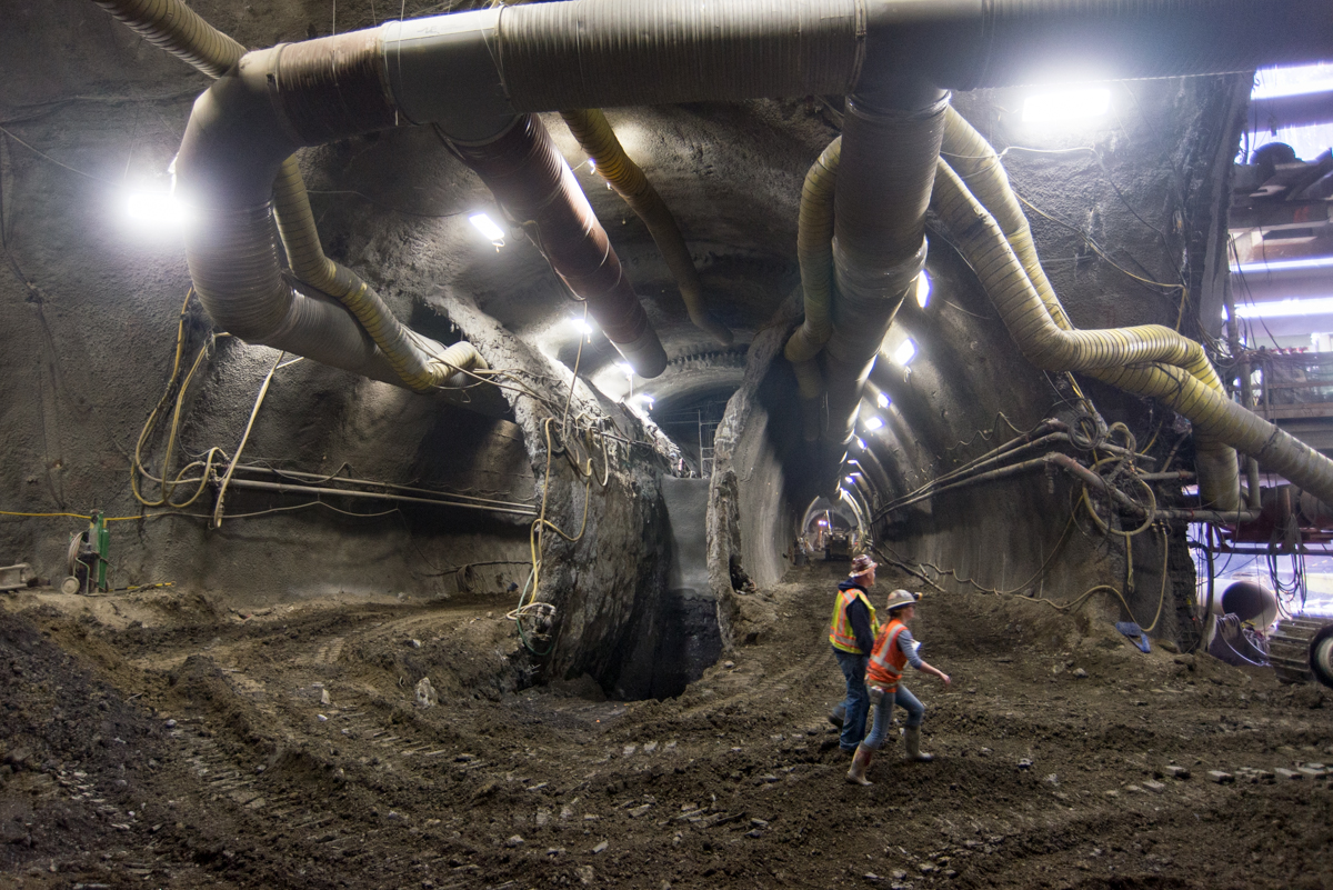 Workers in a gigantic, dirt-floored tunnel.