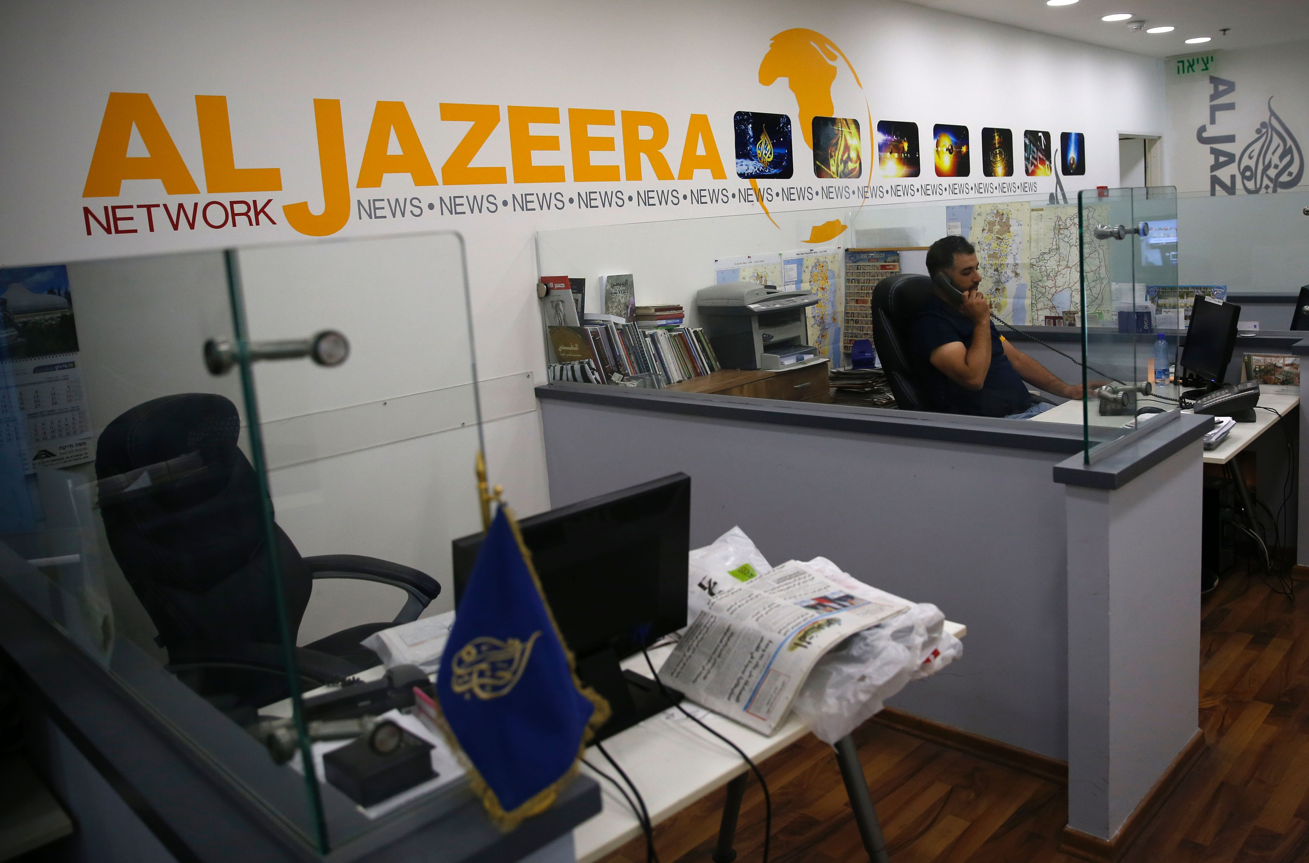"""A man answers the phone in front of a wall with """"Al Jazeera"""" painted on it."""