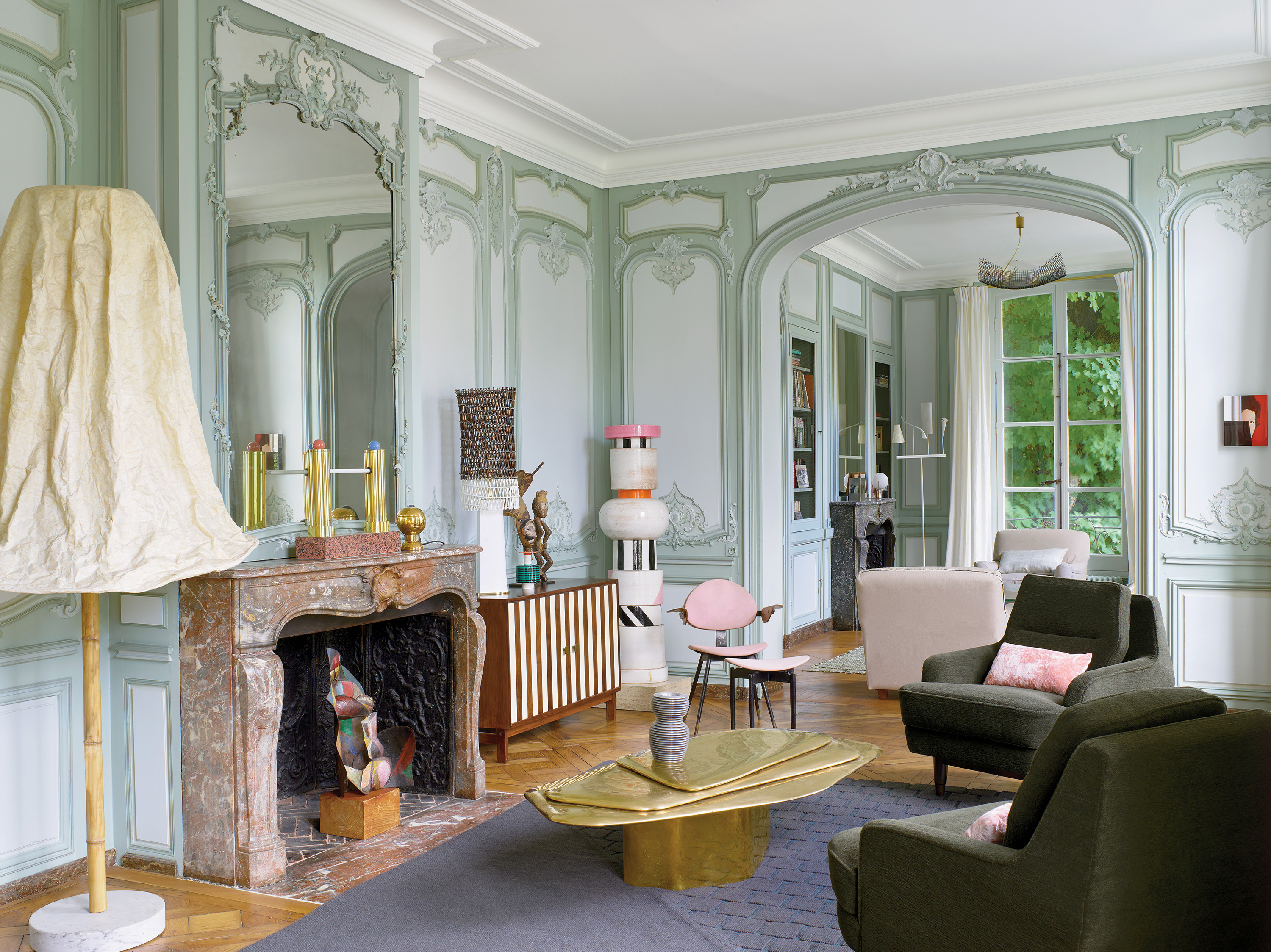 A ceramic stands in the corner of an intricate living room with molding and trim, marble fireplace, and tall French doors among a collection of modern furniture and artwork.