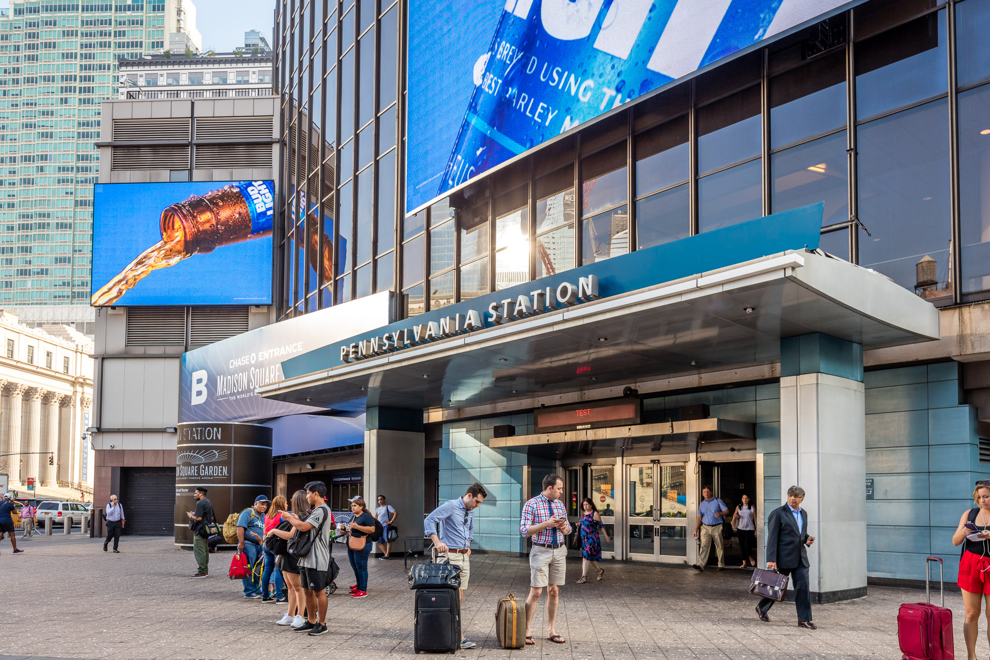 """The exterior of a train station. There is a large sign that says """"Pennsylvania Station"""" over the entrance to the station."""