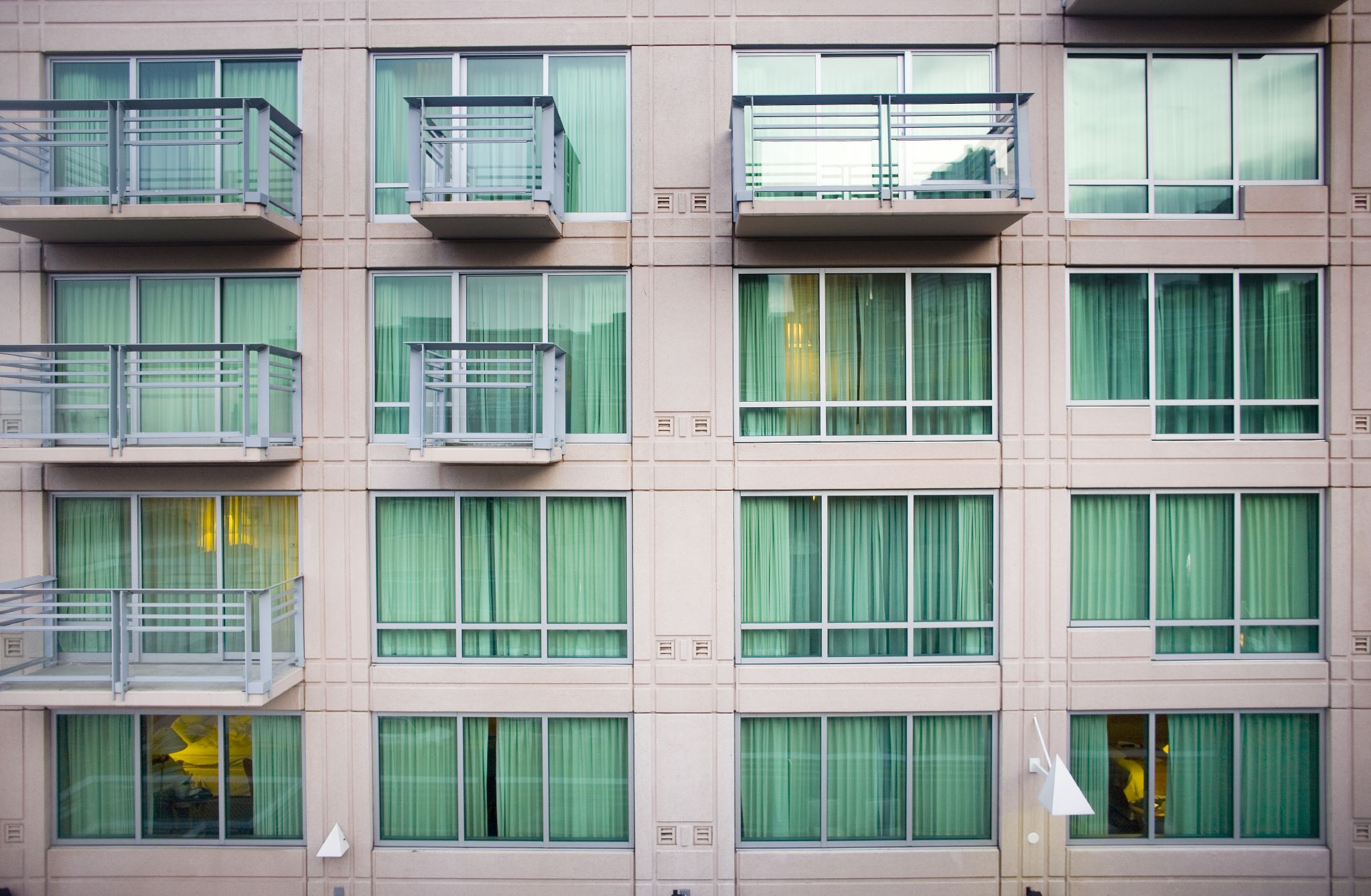 Three rows of floor to ceiling windows on the outside of a beige building with intermittent balconies.