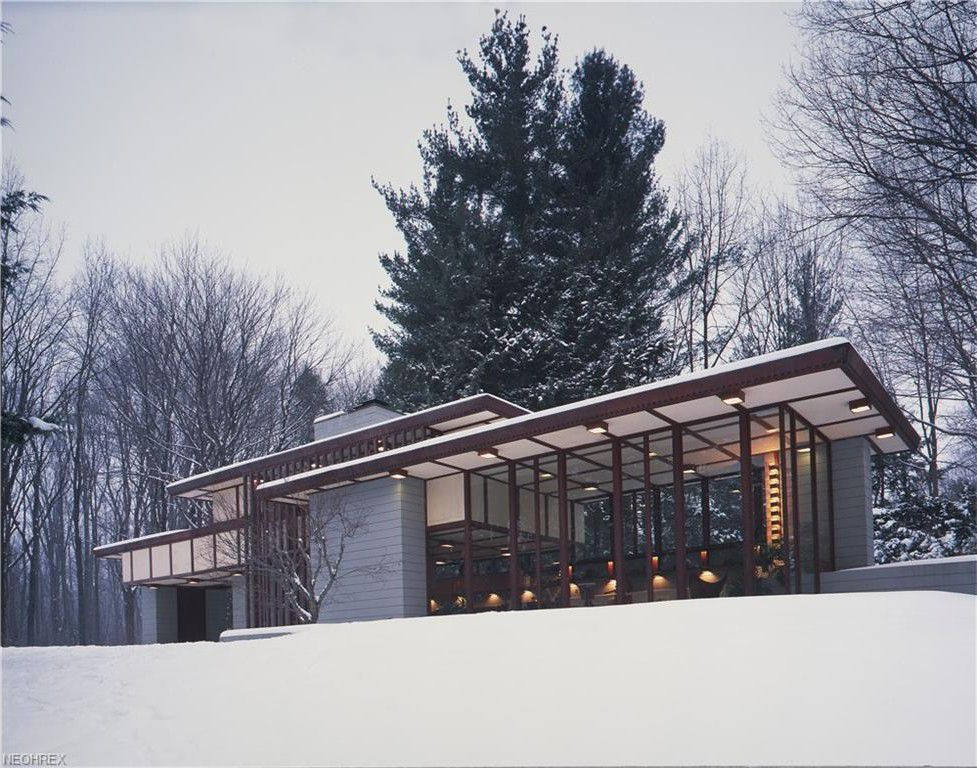 A large windowed house with flat overhanging roof and mortar columns set amid a snowy, wooded site.
