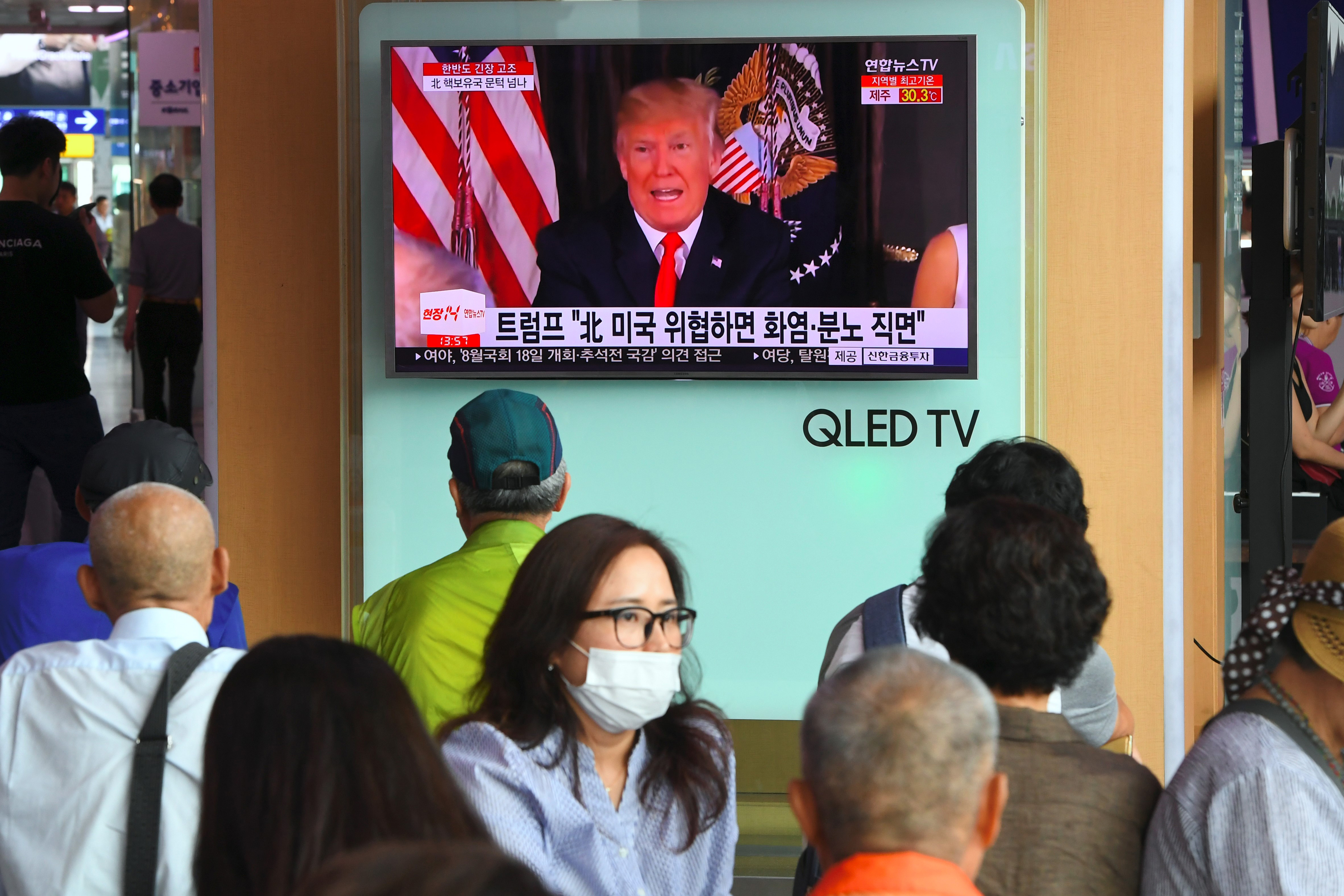 Donald Trump appears on a TV screen with Korean text. People stand watching.