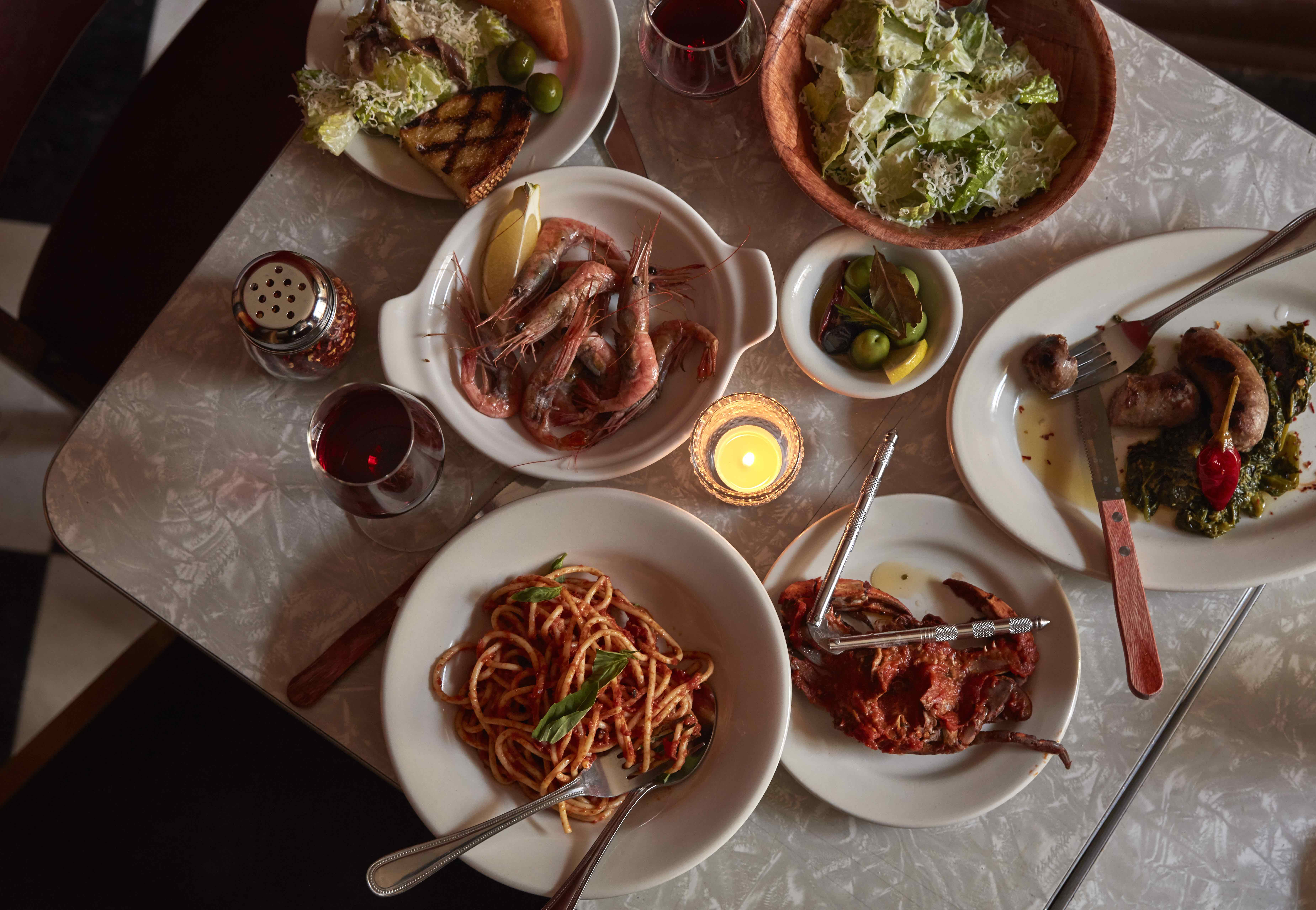 overhead shot of a table with several italian dishes