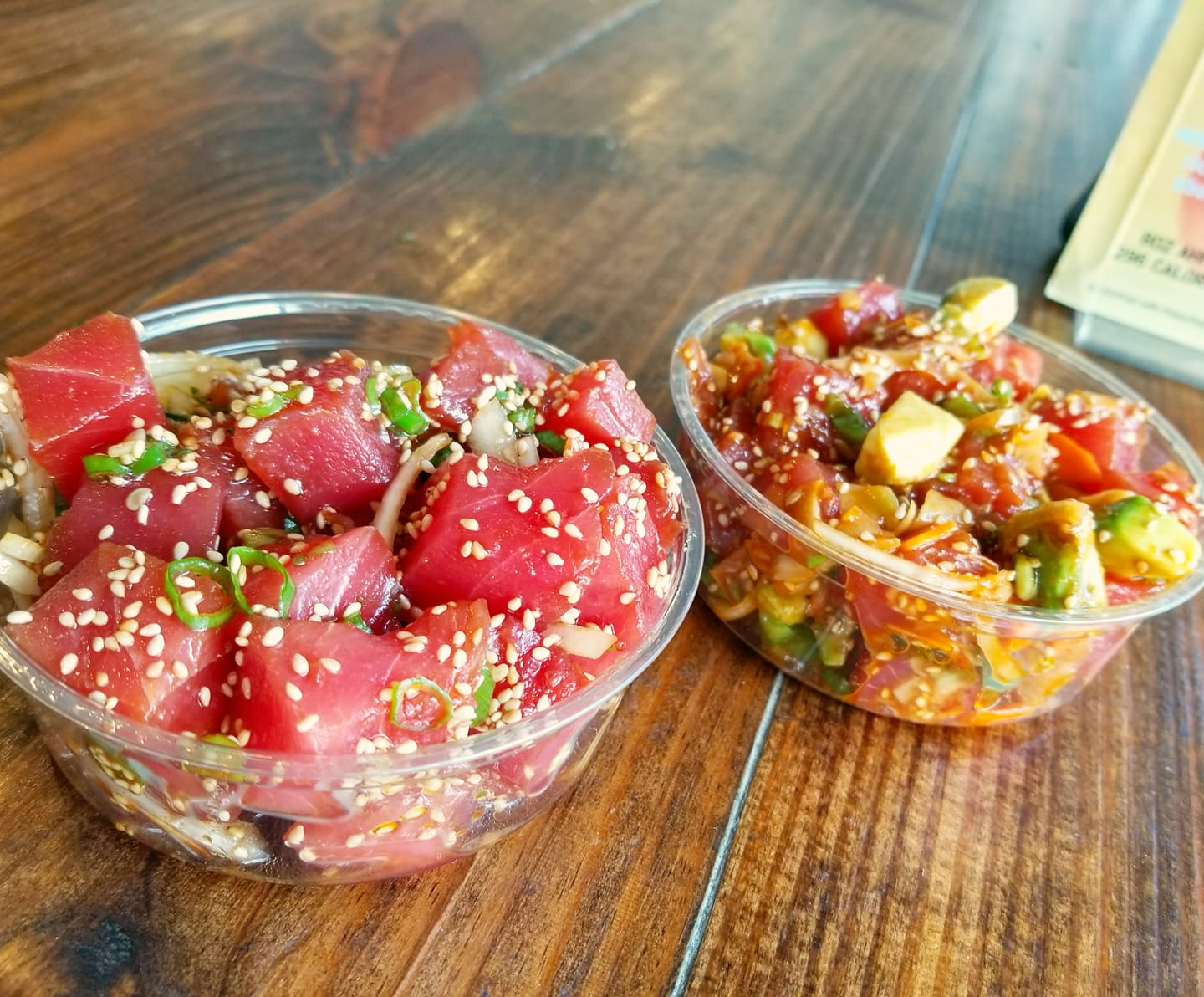 Two open containers of poke from Poke Poke
