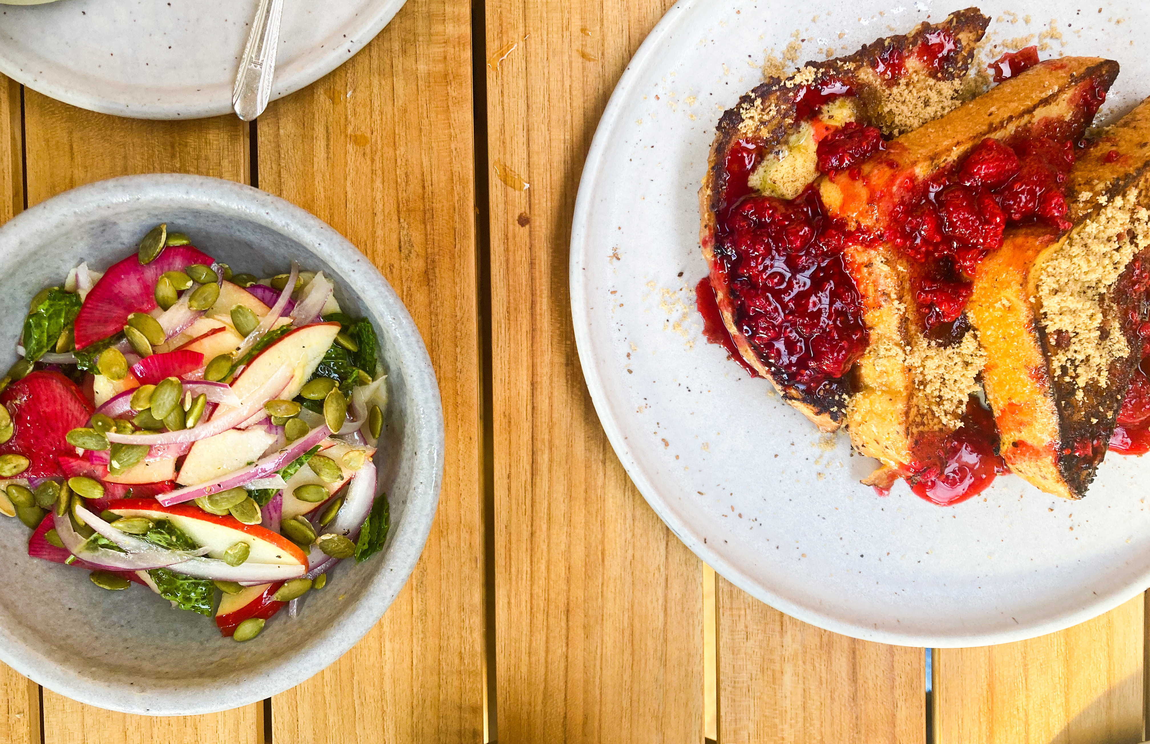 A plate with three slices of french toast, covered in raspberry compote, sits on a wooden table outside Sweedeedee in Portland, Oregon. Next to it, a bowl of sliced apples, radishes, and pepitas sits.