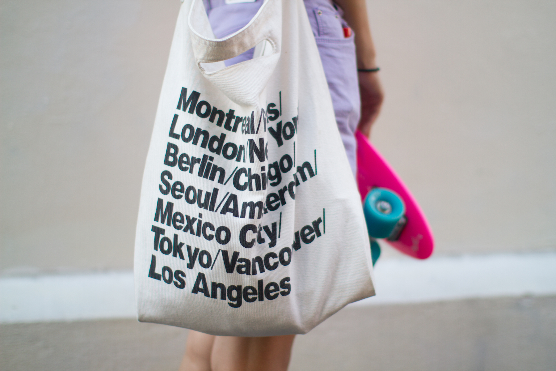 A person carrying a white American Apparel tote bag and skateboard.