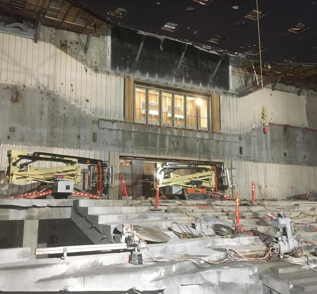 Standing in the middle of where seats used to be, looking toward the back wall of the theater. There is no balcony, but an outline on the wall and a set of doors floating in the air show where it used to be.