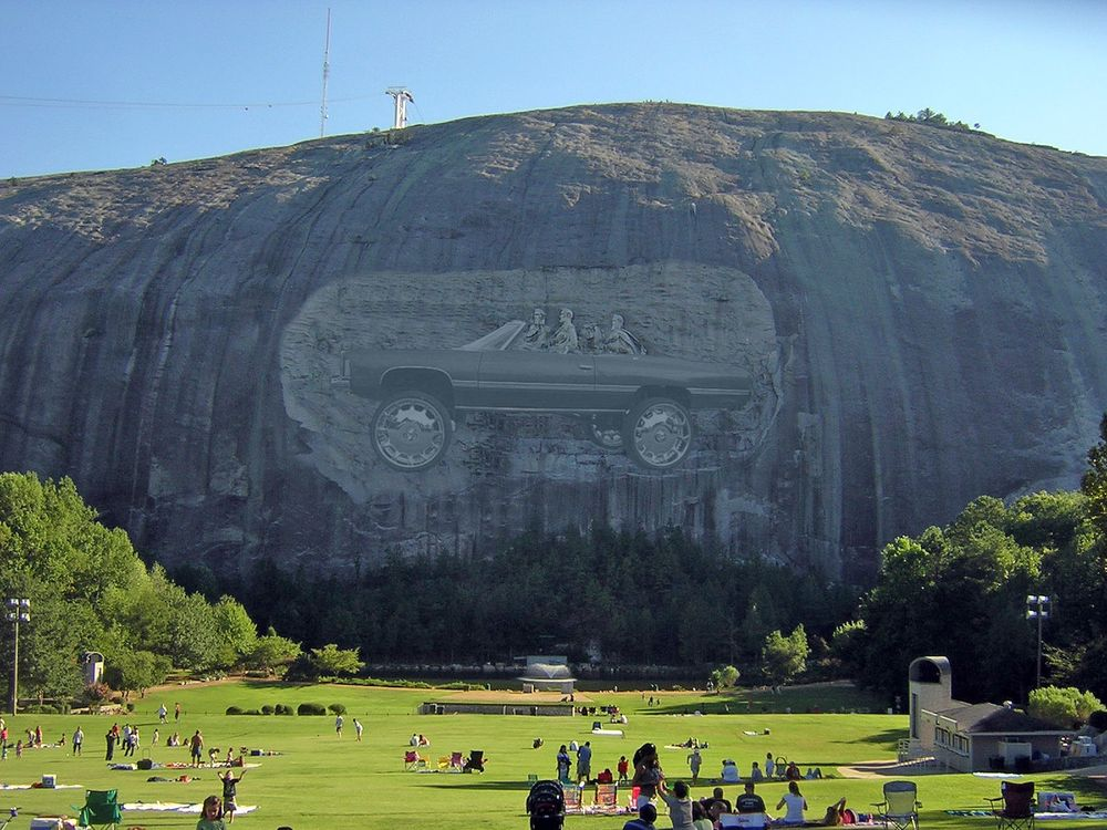 Stone Mountain with the carving's figures appearing to be riding in a Cadillac on 22 inch rims.