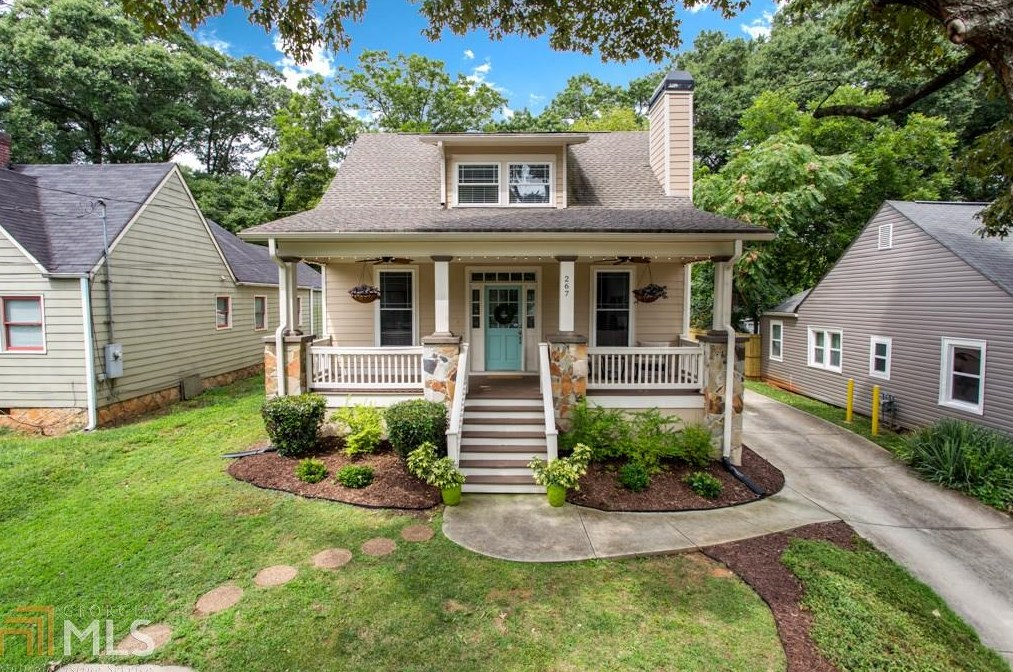Small house with covered front porch and landscaped yard.