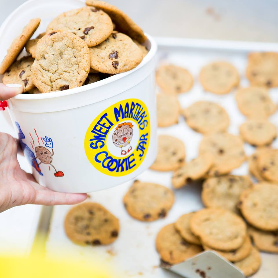 A sheet pan full of chocolate chip cookies with a plastic bucket stacked with cookies in the foreground, held by a hand with red fingernail polish