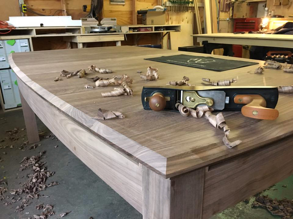 A planar and woodshavings perched atop a Wyrmwood gaming table. The photo was taken in their Mass. workshop.