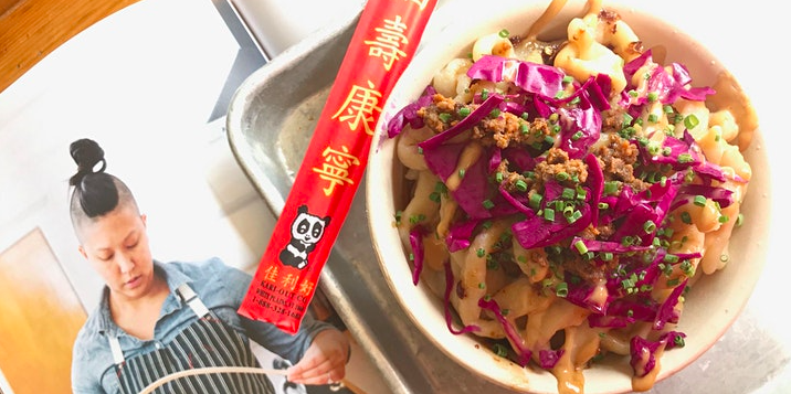 A bowl of hand-pulled noodles topped with scallions, ground pork, and red cabbage sits on a metal tray with a pair of disposable chopsticks. The tray is next to an open book with a photograph of a woman stretching noodles.