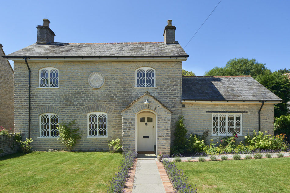 Stone house with lattice windows and round carved lion face on facade sits behind manicured lawn.