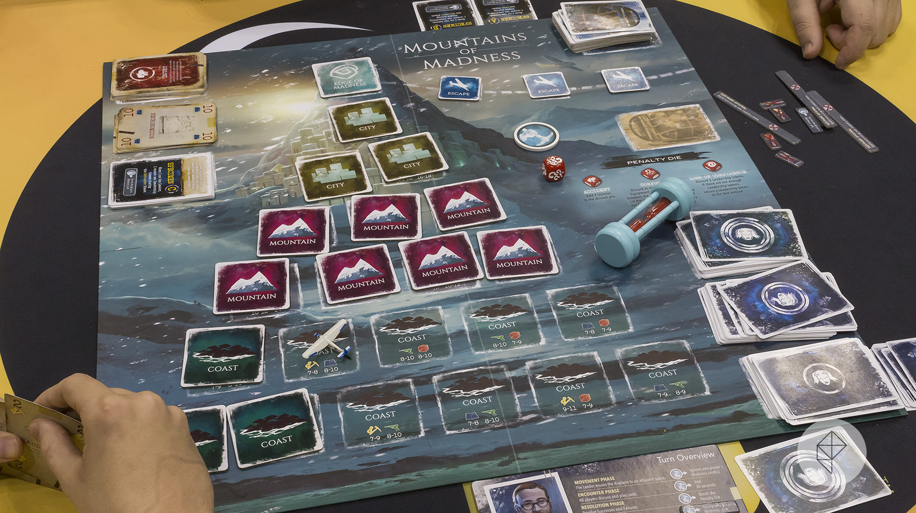 A pyramid of cards sits face down on the game board representing the mountain itself. A sand timer sits to one side.