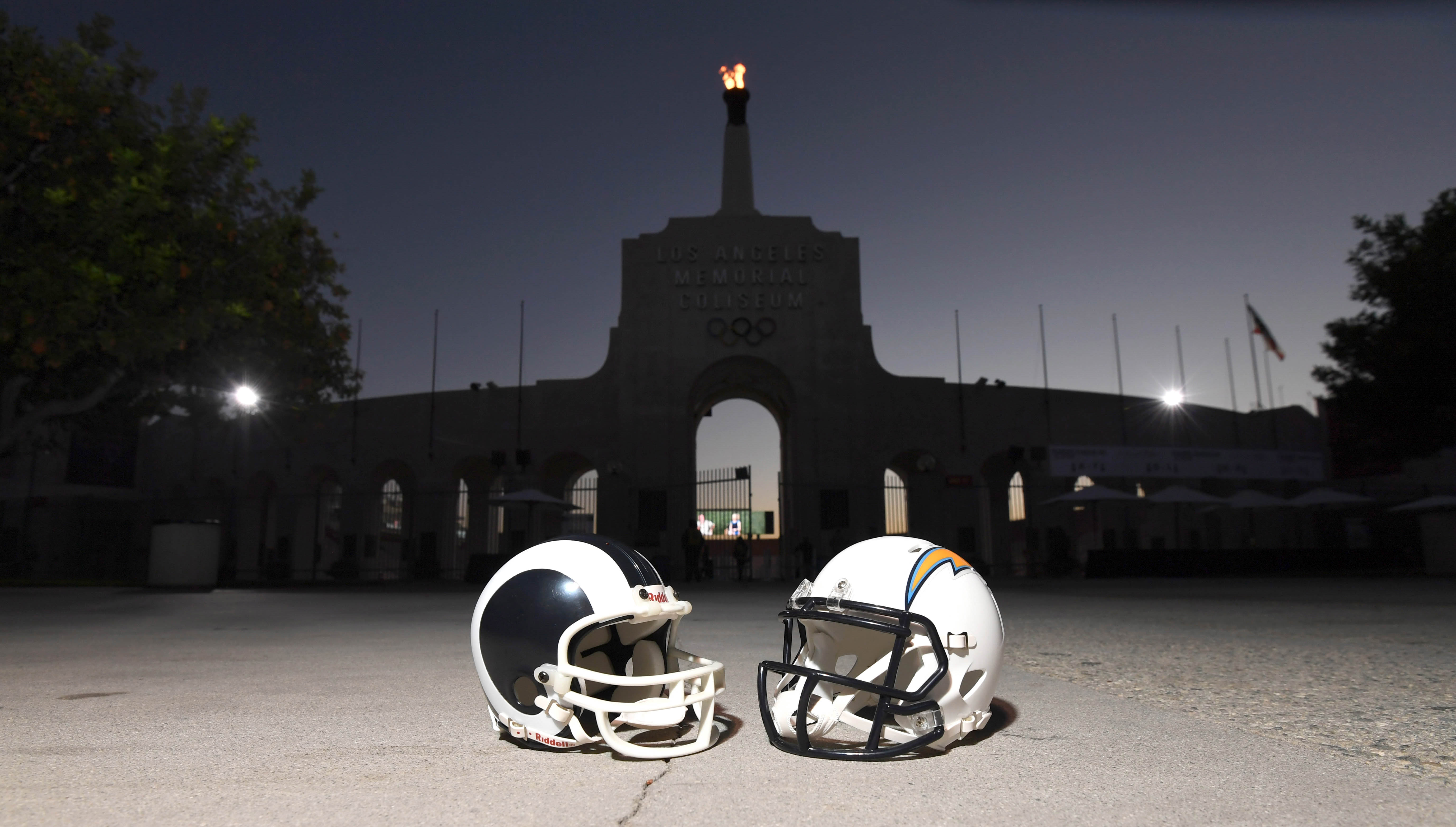 Los Angeles Rams & Chargers helmets in front of the Coliseum