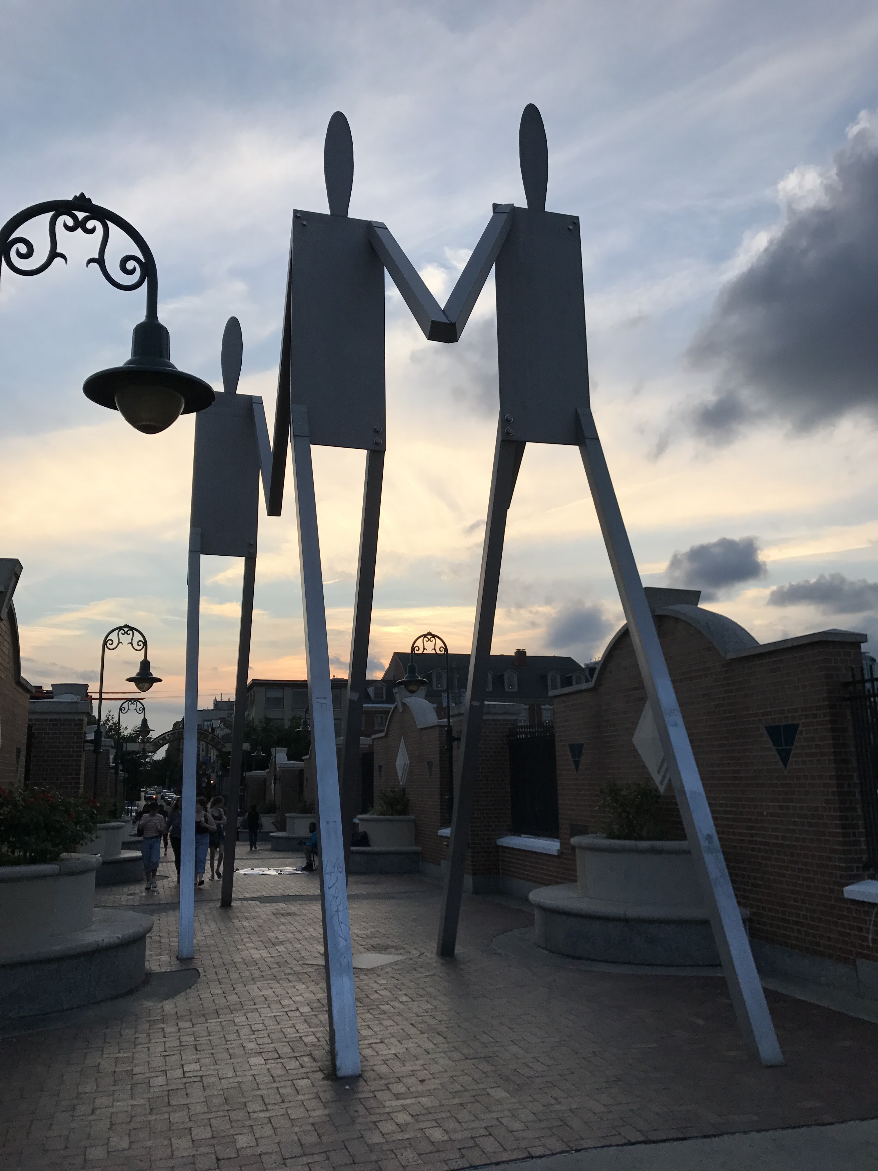 Public art installation of human-esque figures walking, taken at sunset.