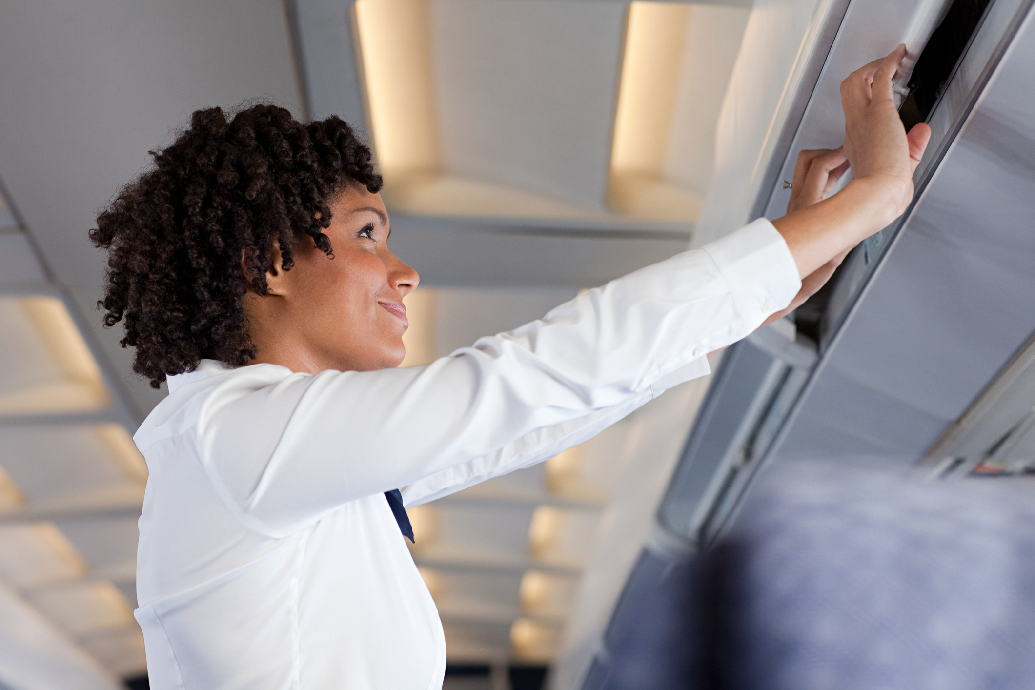 A flight attendant putting a suitcase in the overhead compartment
