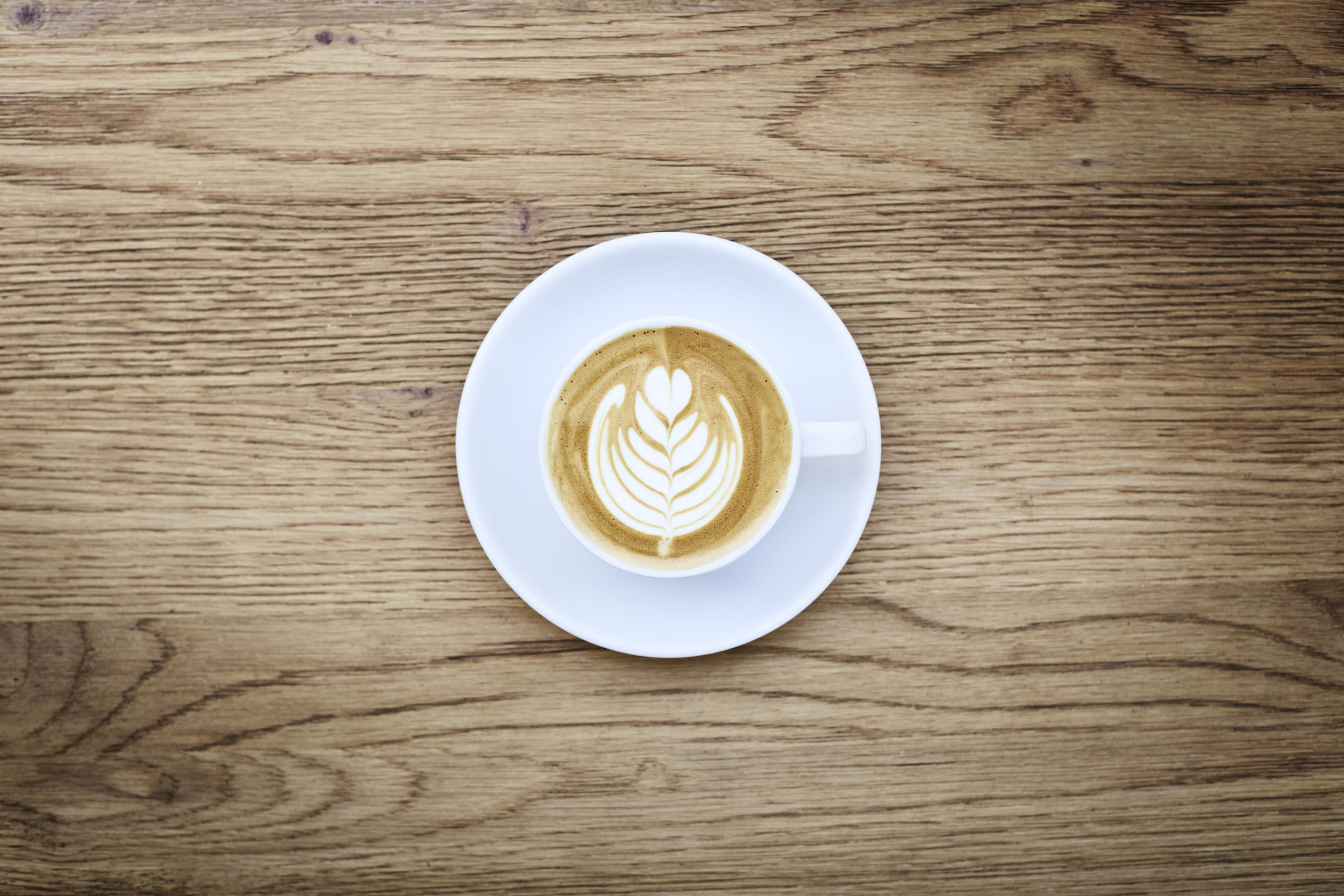 A flat white coffee in a white ceramic cup on a wood background