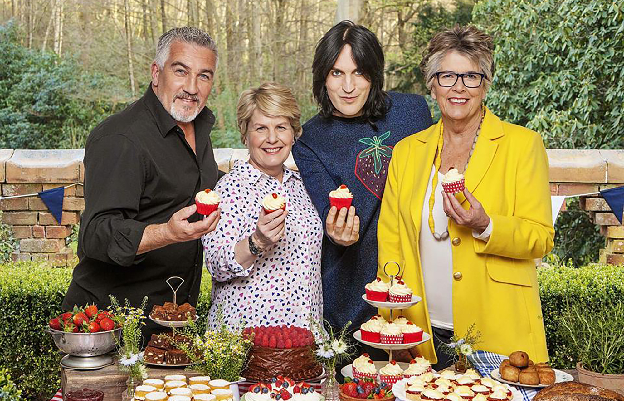 Paul Hollywood, Sandi Toksvig, Noel Fielding, and Prue Leith stand in front of a table filled with pastries holding up cupcakes with cherries on top.