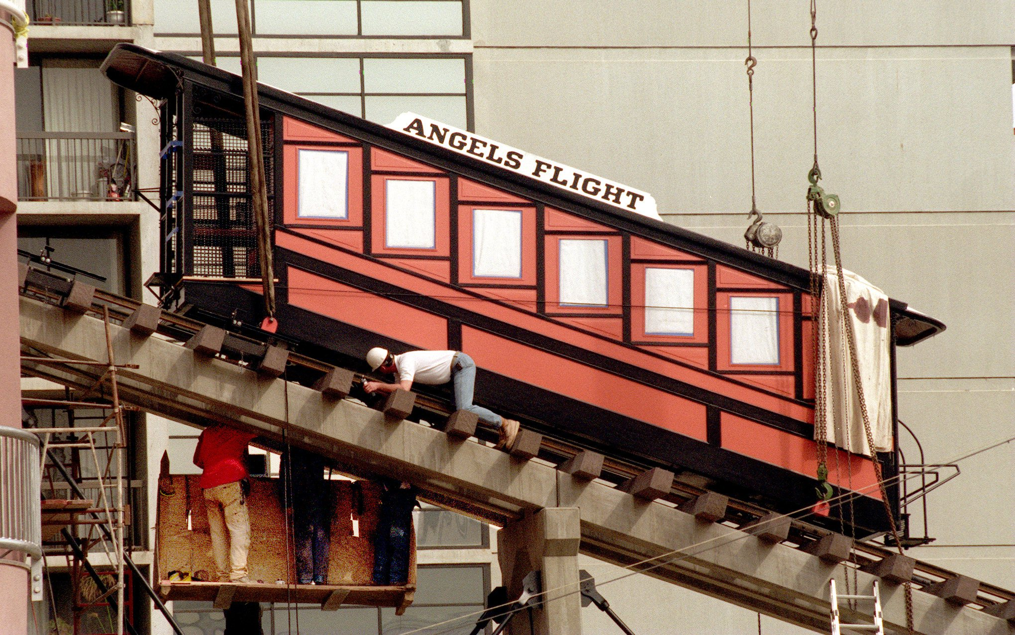 Workmen attach cables that will lift and lower 'Sinai,' the second of the twin cars of the historic Angels Flight placed on the inclined railway tracks linking Hill Street with Bunker Hill on Olive Street.
