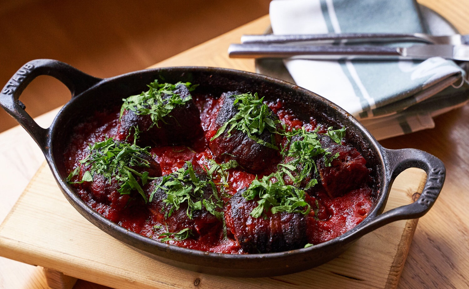 Six dates sitting in red sauce in a cast iron skillet.