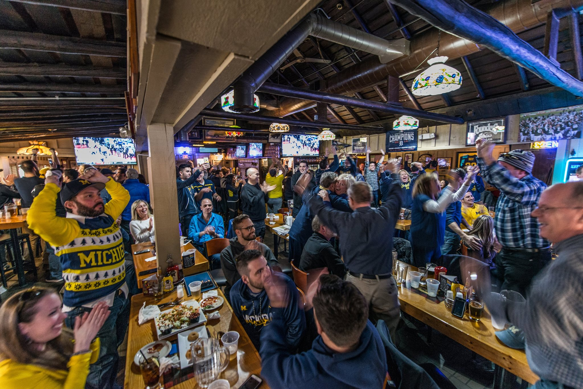 U-M fans dressed in blue and maize back the house at Fraser's Pub and cheer during a football game.