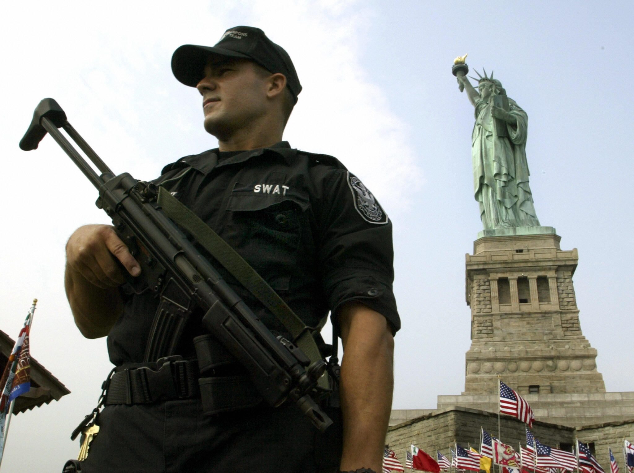 A police officer stands guard in front of the Statue of Liberty.