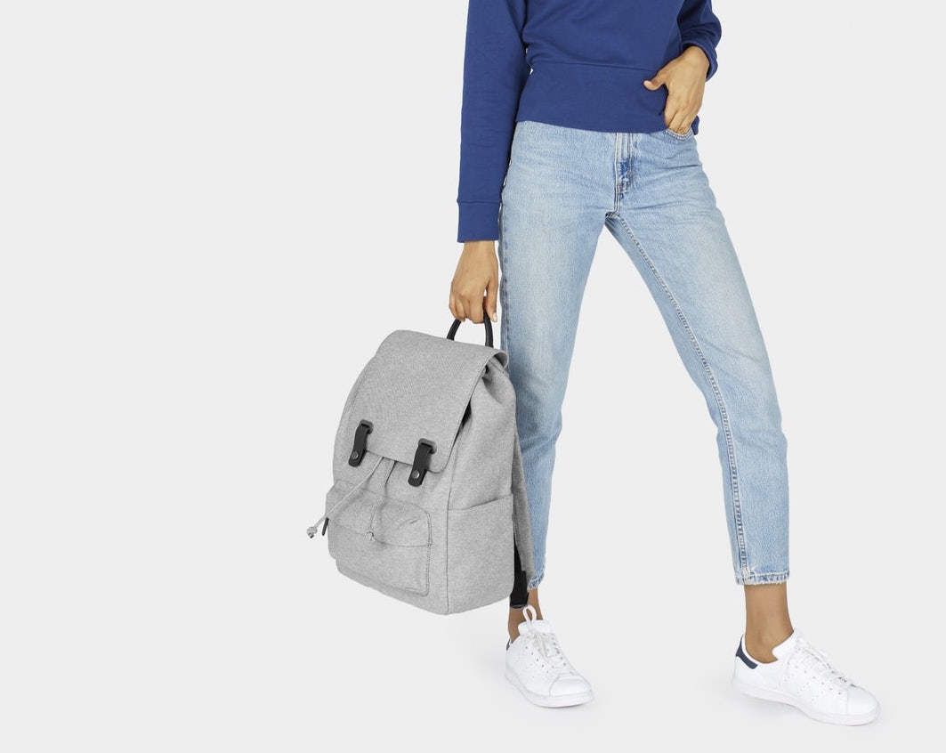 A model in jeans and a blue sweatshirt holding a gray backpack