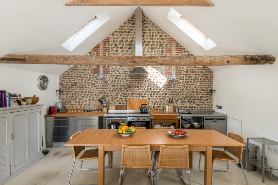 Interior shot of vaulted kitchen with exposed brick wall behind simple steel and butcher block kitchen space, white walls otherwise, wooden dining table, and wide-plank painted floorboards.