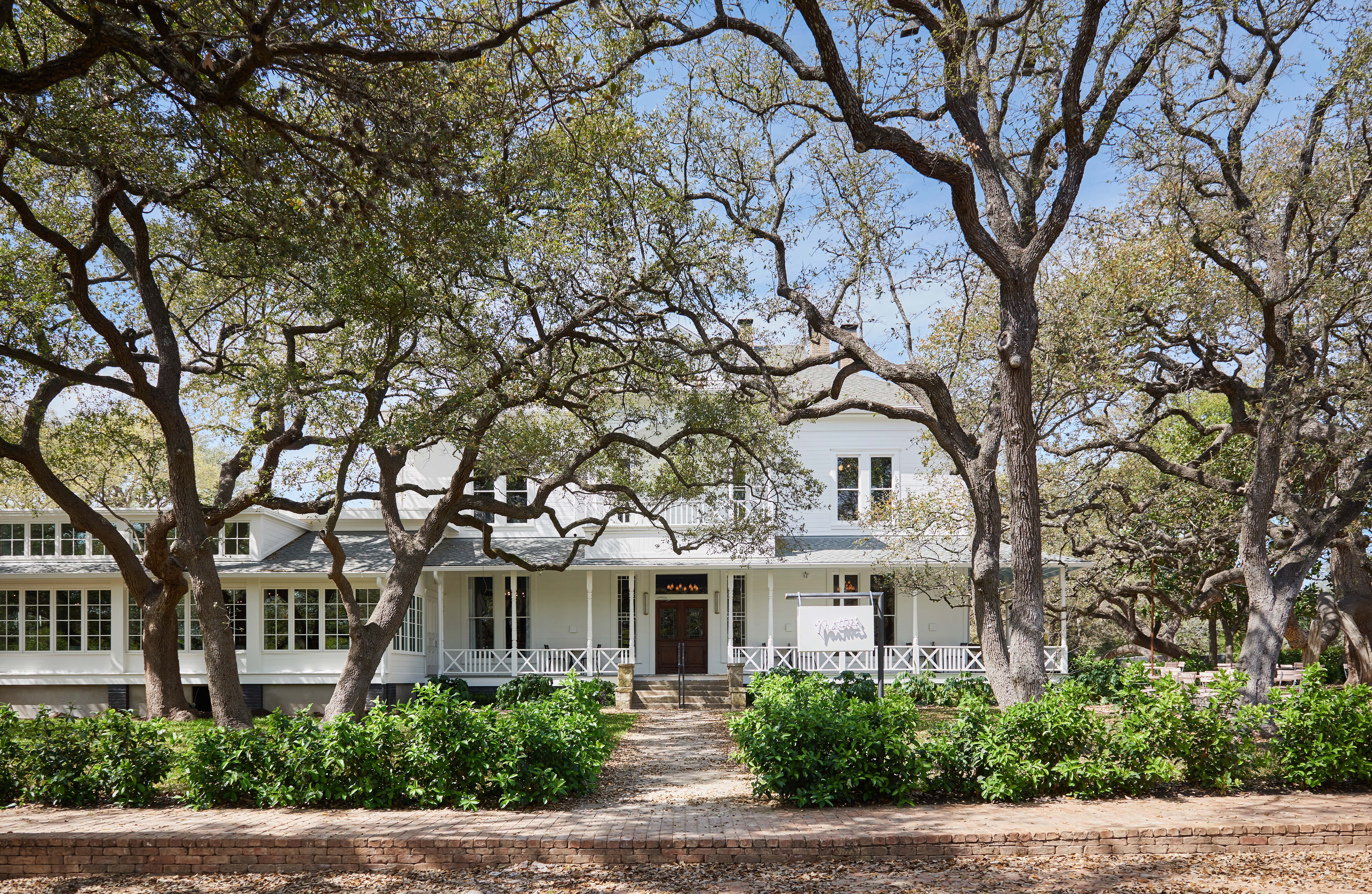 Photo of white Victorian house/restaurant with large oaks