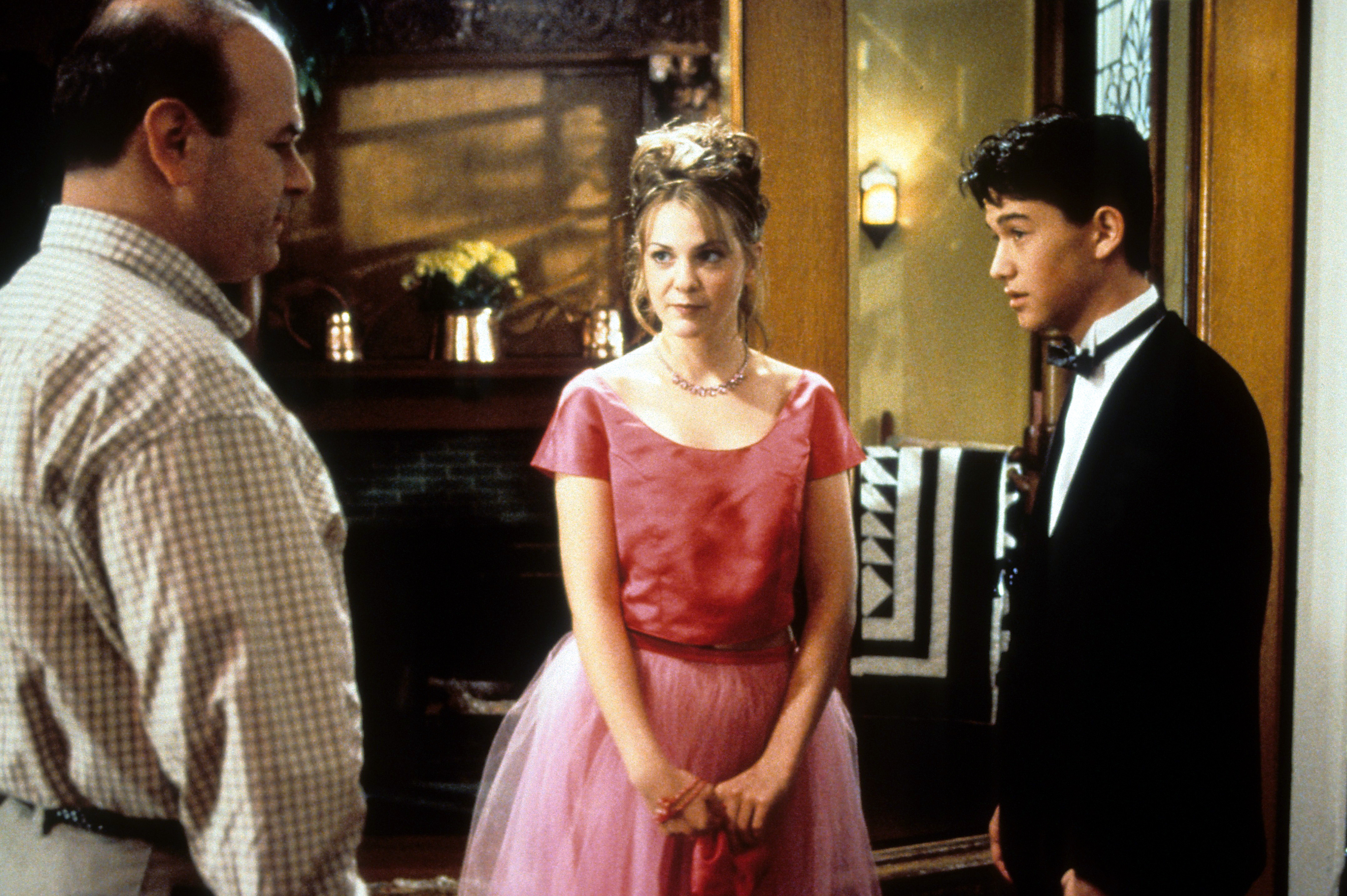 A young man in a tuxedo and a young woman in a pink prom dress speak with a balding man in a plaid shirt.